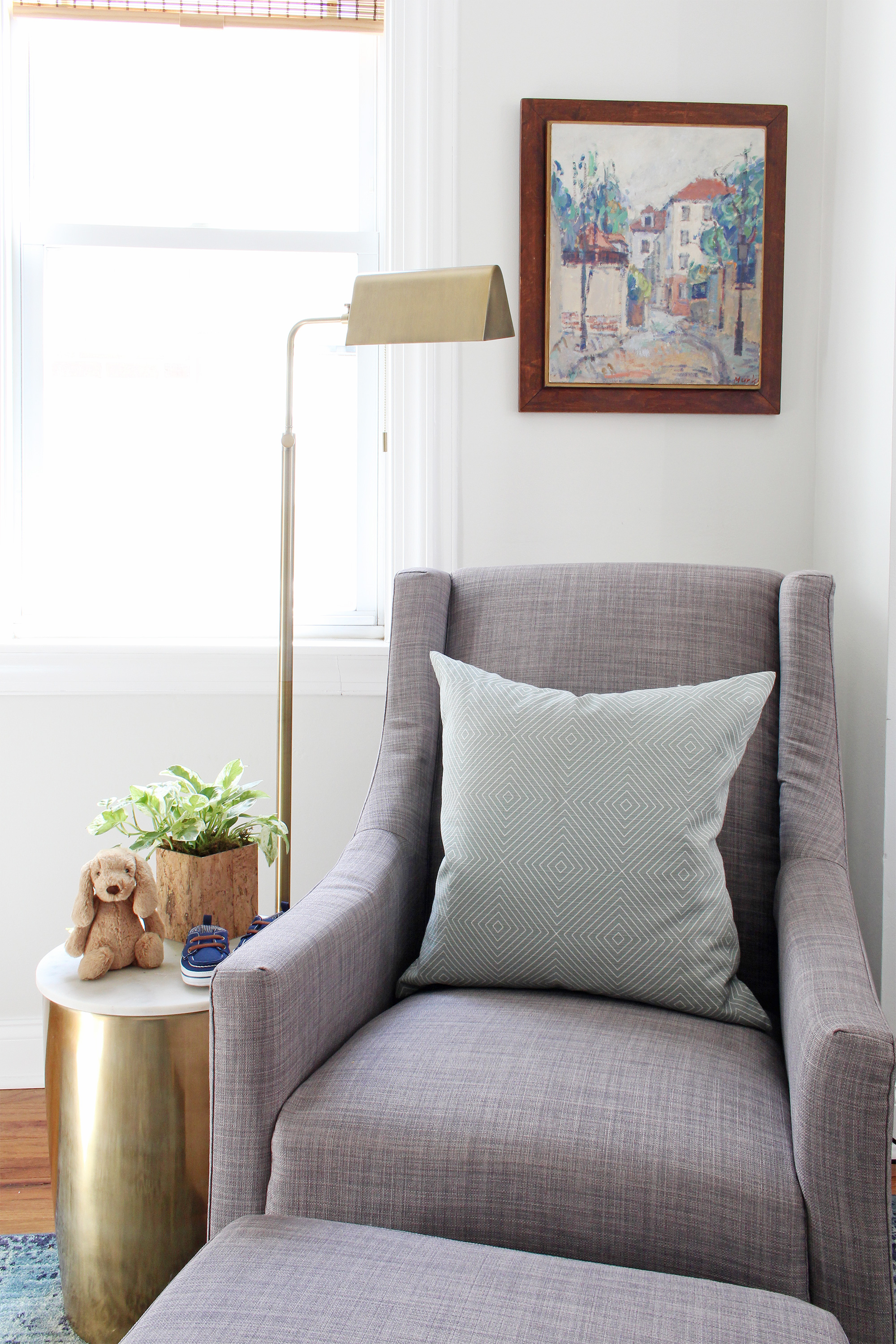 "Come on over to the Mix & Match Design Company blog for this cozy modern nursery nook reveal! This space is shared with a home office and is full of great ideas on how to squeeze in a small nursery into a closet. The ""nursery nook"" concept is perfect if you live in a smaller home. Gray glider with brass side table."
