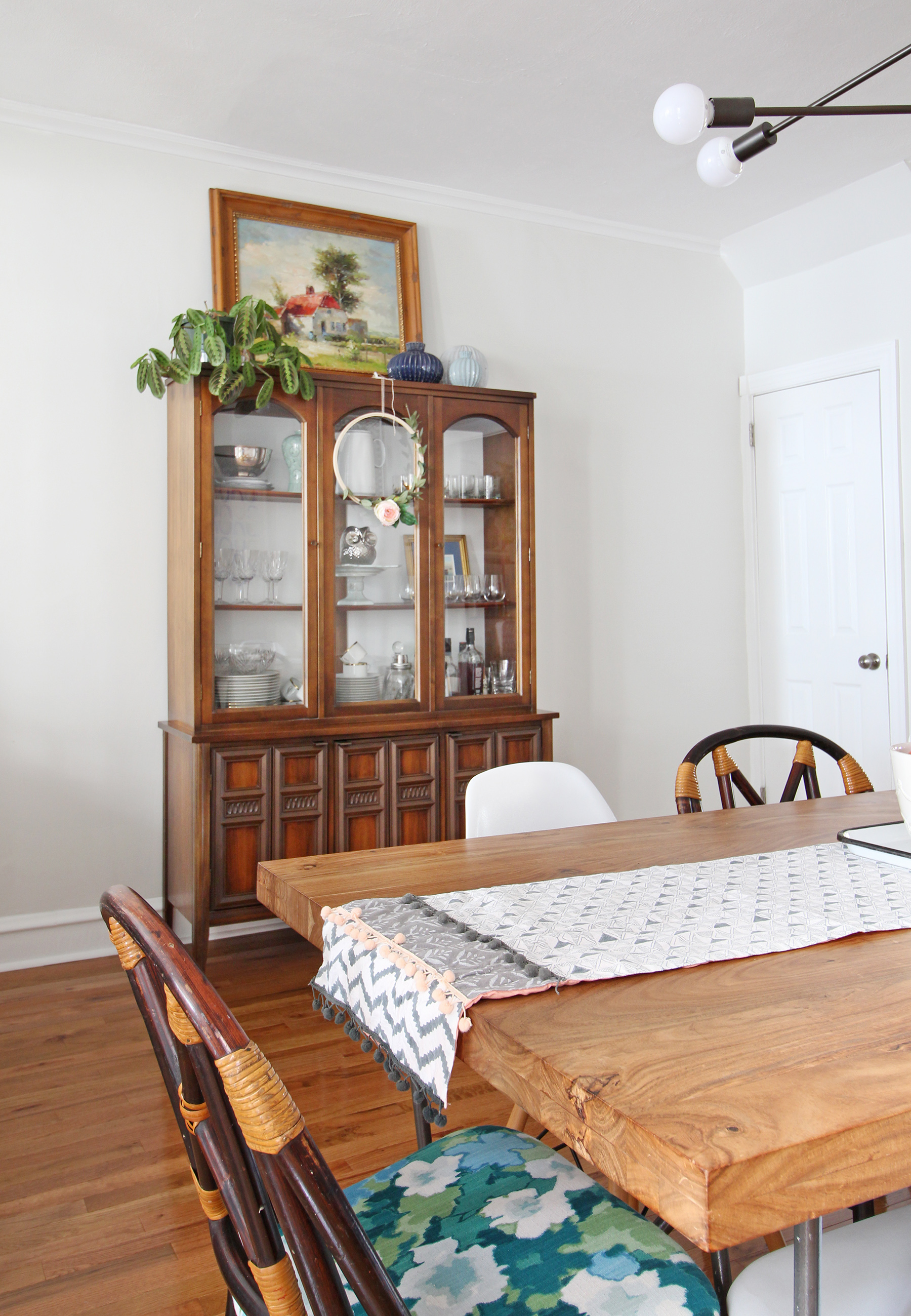 A 1930s row home in Philadelphia gets a big makeover. Come see the before and after of this home's living, dining, and kitchen open floor plan and get ideas for small space city living. Chaney's style is mid-century modern meets traditional that makes for an eclectic, cozy space. A dining table for 8 and a mid-century storage cabinet complete the dining area.