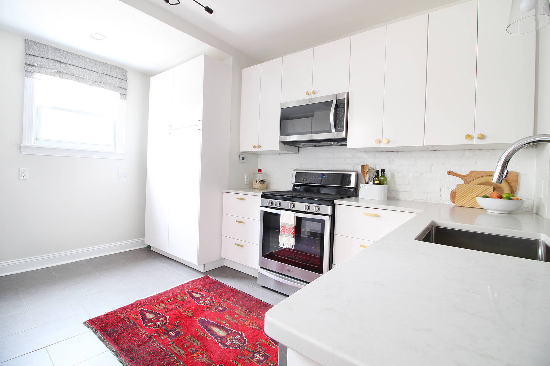 A 1930s row home in Philadelphia gets a big makeover. Come see the before and after of this home's living, dining, and kitchen open floor plan and get ideas for small space city living. Chaney's style is mid-century modern meets traditional that makes for an eclectic, cozy space. The bright and airy modern kitchen opens up to the rest of the first floor.