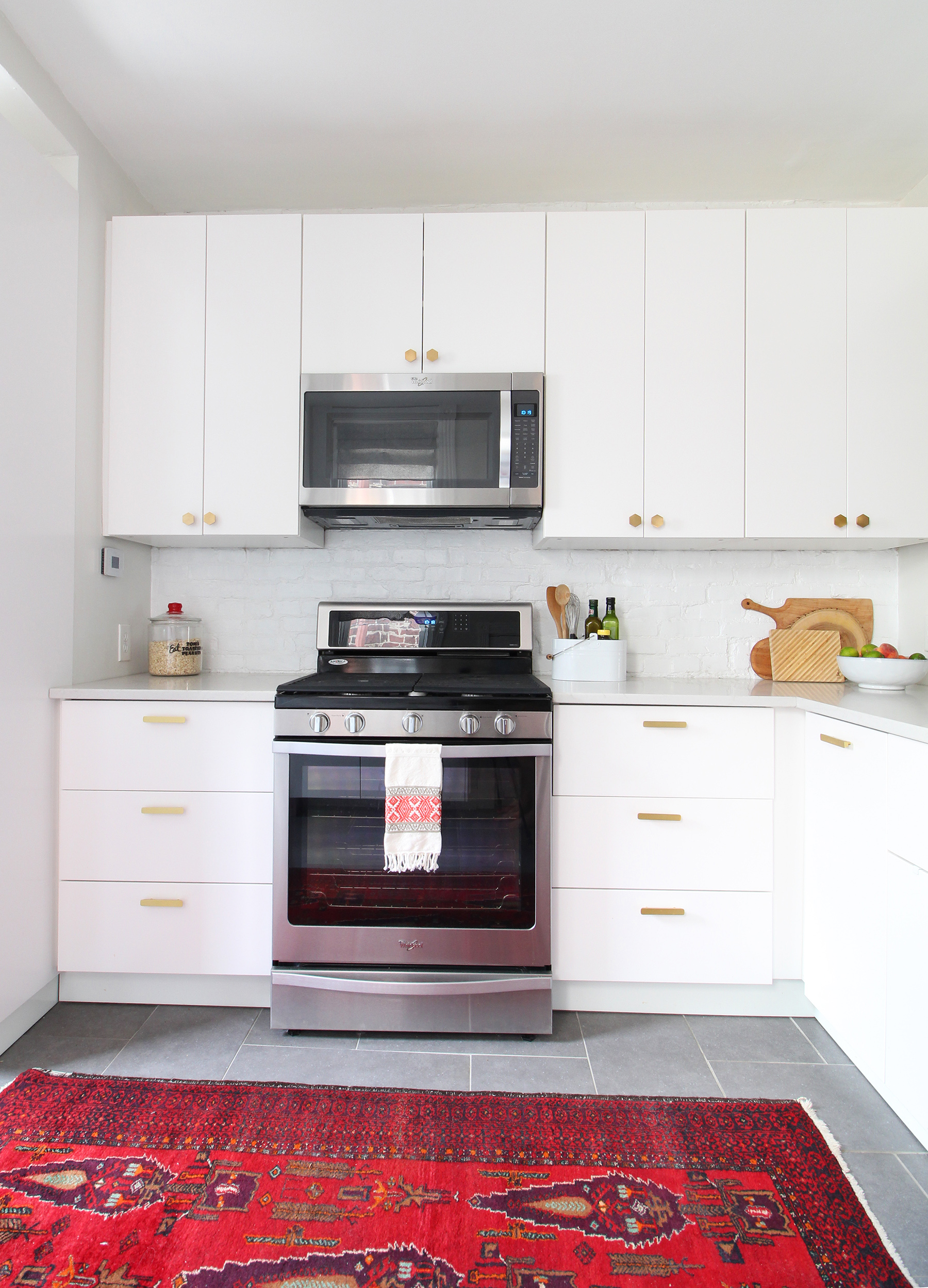 A 1930s row home in Philadelphia gets a big makeover. Come see the before and after of this home's living, dining, and kitchen open floor plan and get ideas for small space city living. Chaney's style is mid-century modern meets traditional that makes for an eclectic, cozy space. A modern kitchen with white cabinets and quartz countertops.