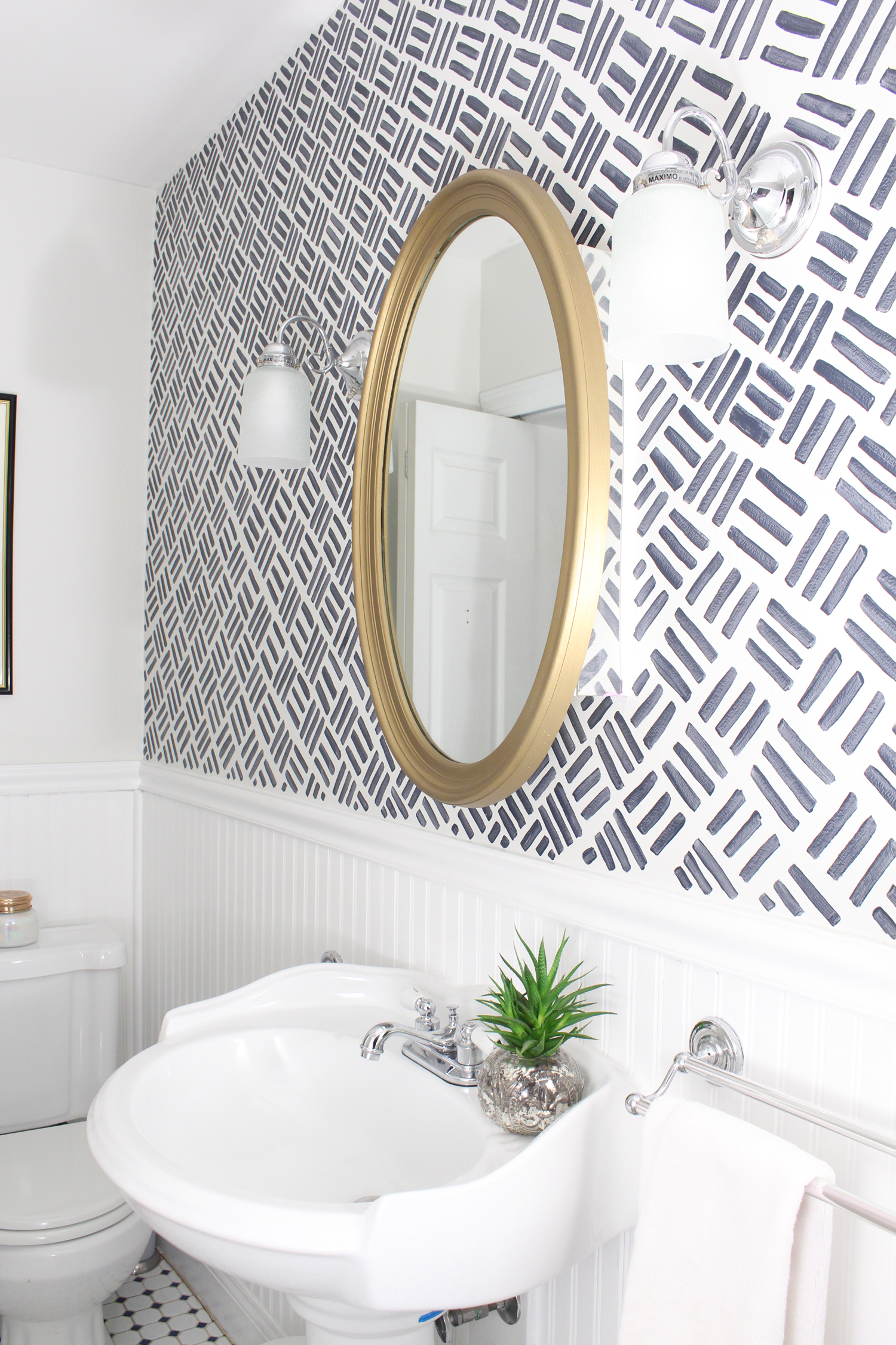 A 1930s row home in Philadelphia gets a big makeover. A purple bathroom got a hand-painted wall treatment with a blue hash pattern. Come see the before and after!