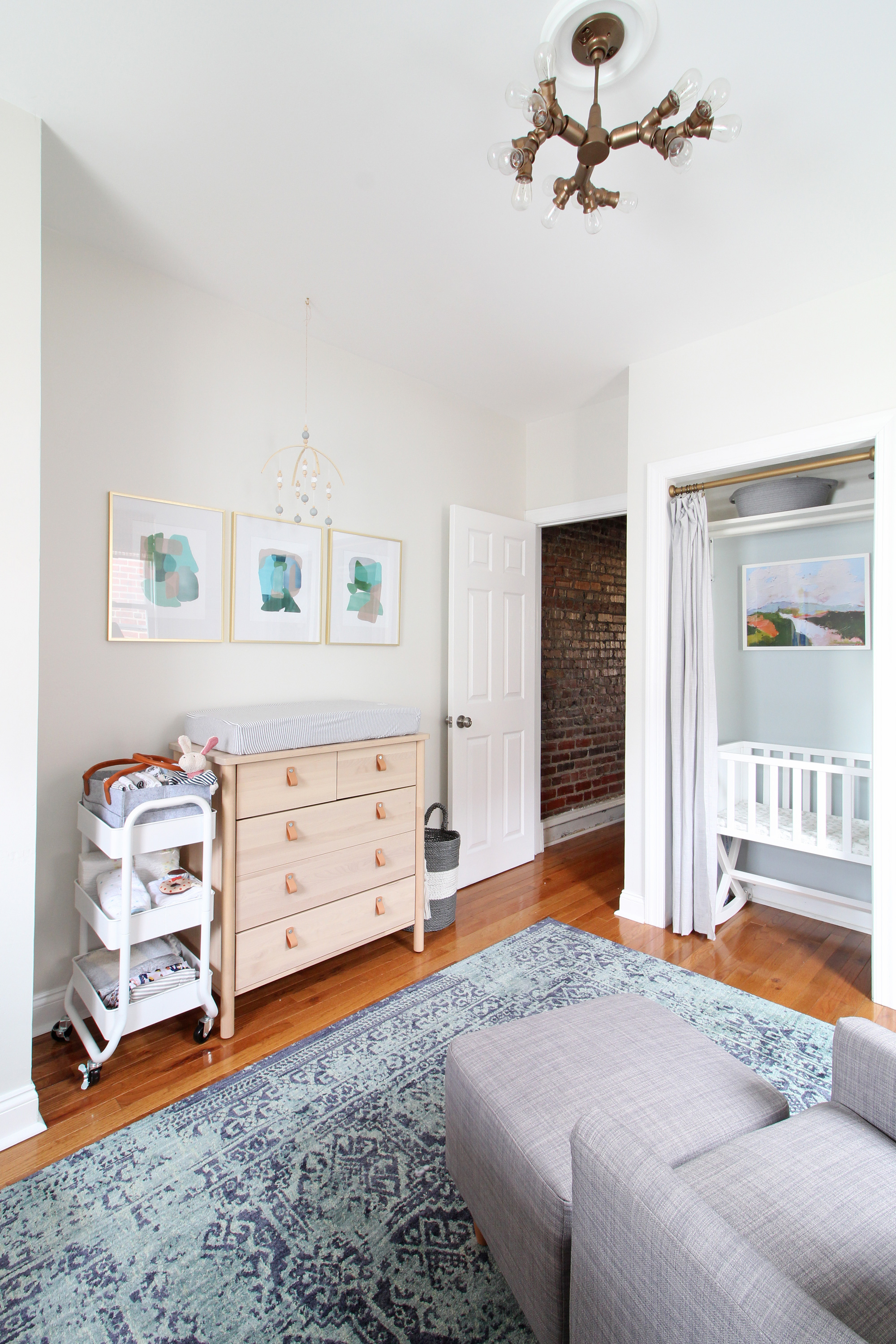 A 1930s row home in Philadelphia gets a big makeover. Come see the before and after of this home's bedrooms, small bathroom, and office/nursery nook. Get ideas for small space city living! This nursery is shared with a home office and has a cozy modern style.