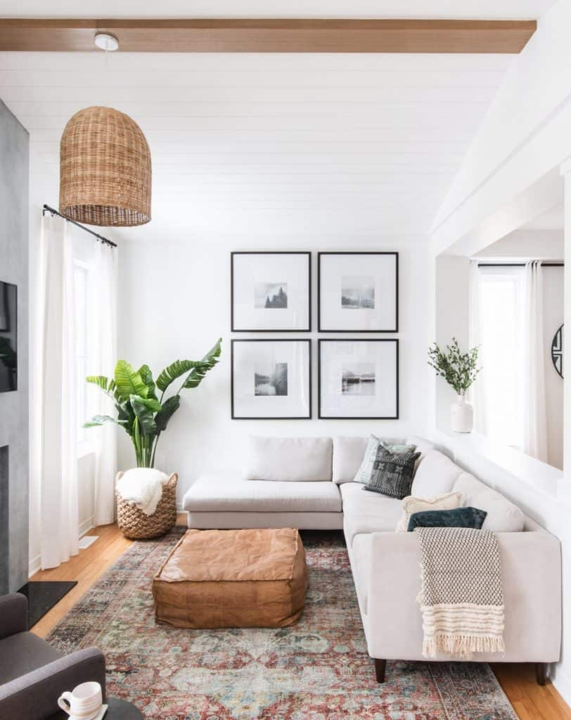 Rattan pendant hangs in a modern traditional living room with a vintage rug. The white sectional pairs perfectly with a leather ottoman. By Leclair Decor