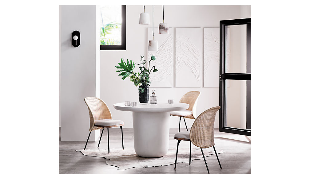 Beautiful cane and rattan dining chairs in a modern dining room with the white pedestal table.Chairs from