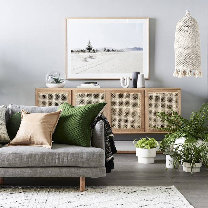 Gorgeous woven door sideboard (cane) in a modern living room. Love the gray sofa with moroccan style rug and the oversized landscape art above the sideboard.