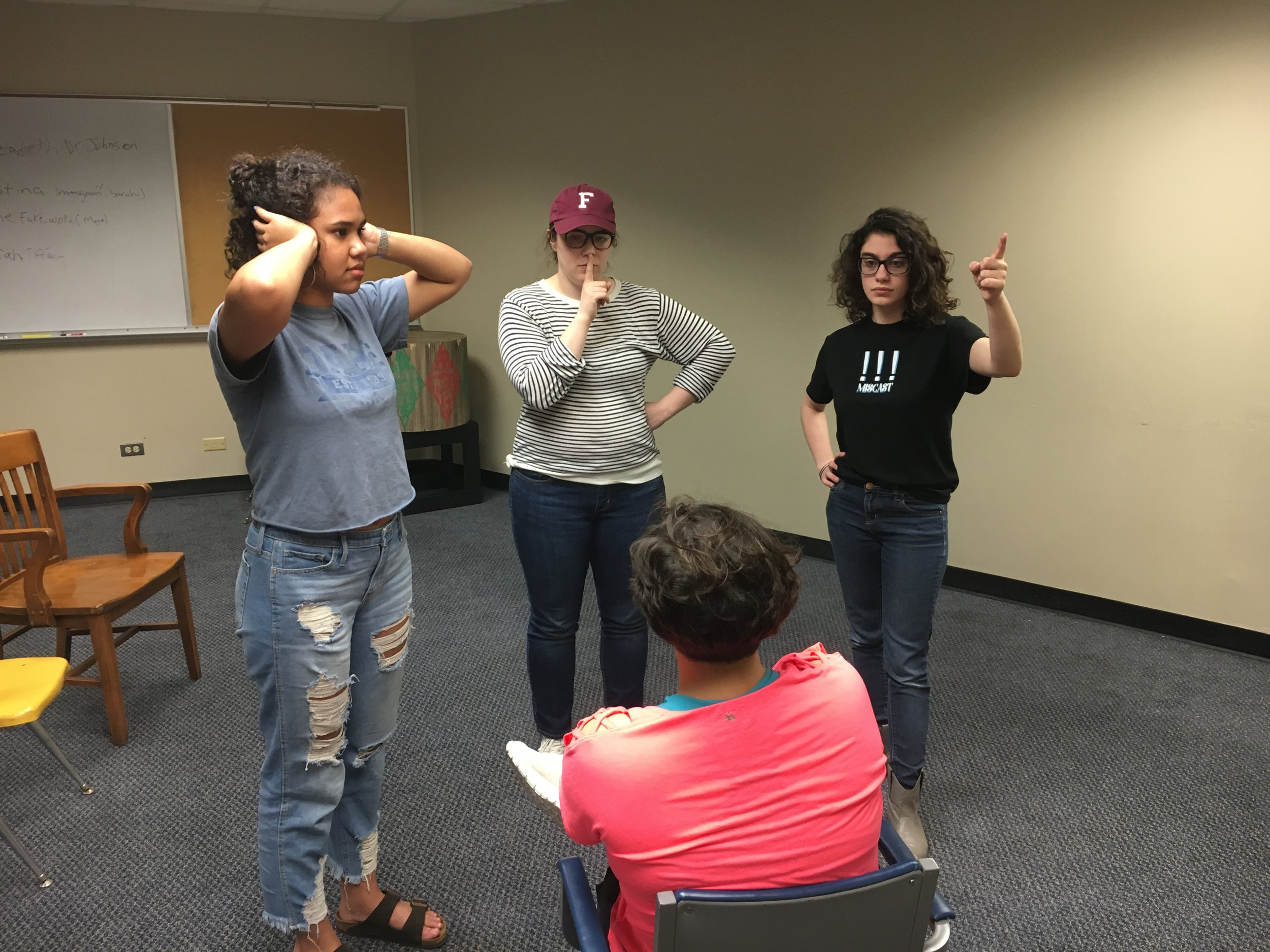 The first image shows what the actors thought the oppression looked like at its worst. The immigrant is in the chair while one of the classmates has her hands over her ears and the other one is pointing for the immigrant to leave. The professor is telling the immigrant to be quiet. After taking a picture and talking about it, they were asked to make the oppression even worse. This is portrayed in the second image.