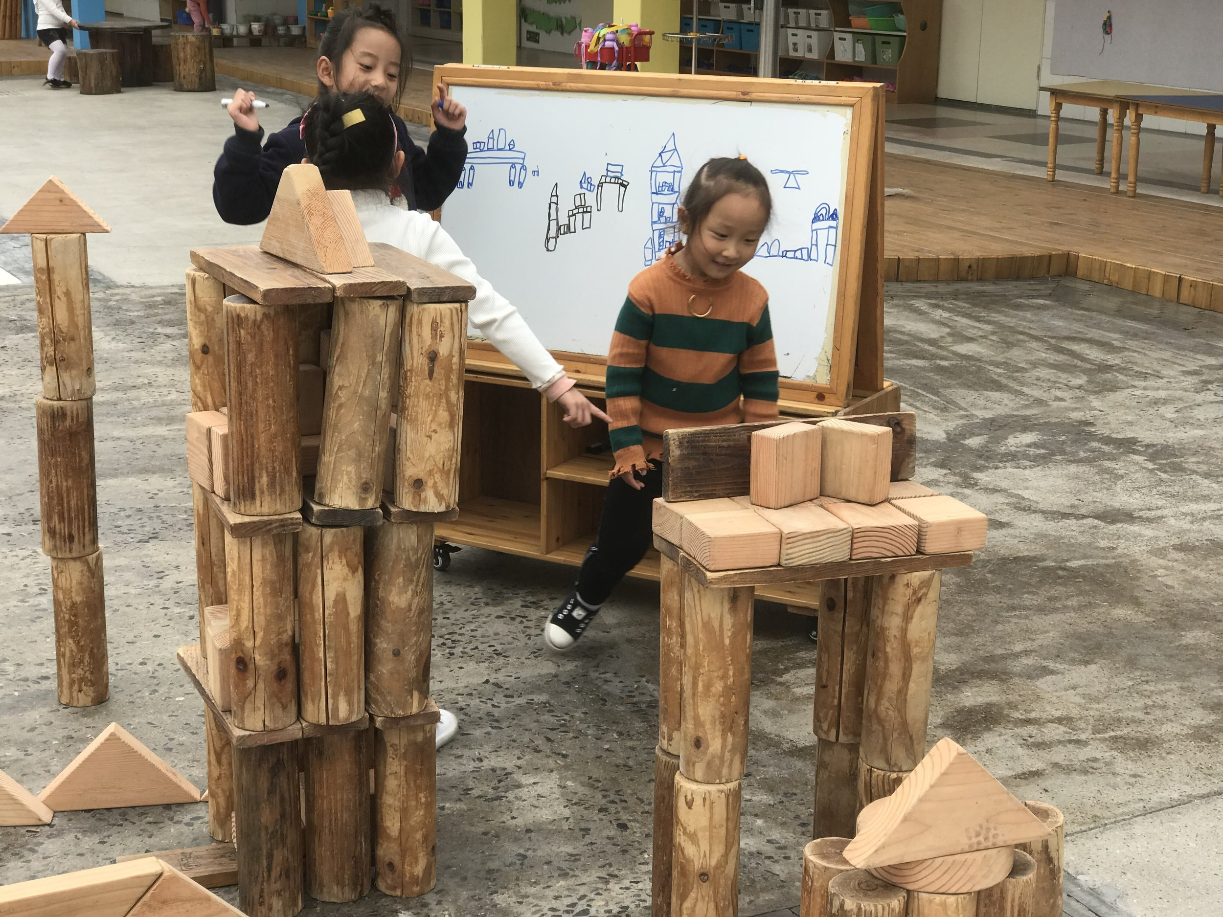 Children in Anji work on a Play Plan. After self-selecting groups, children have access to materials that allow them to plan their block play.