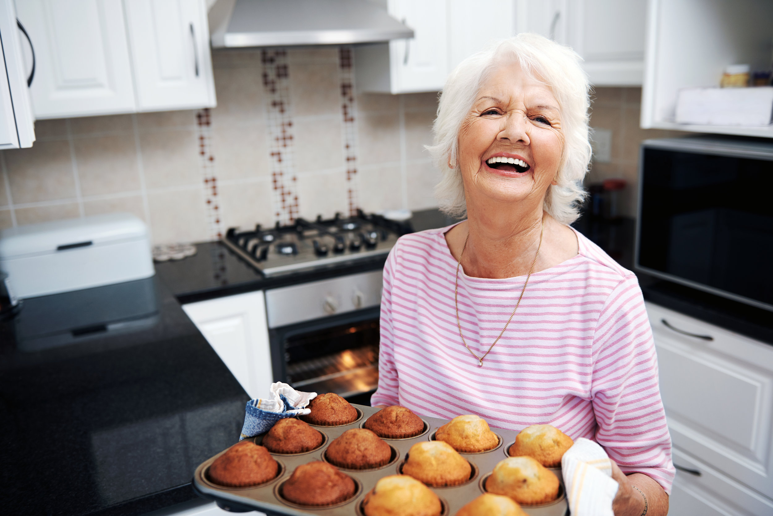 an elderly woman holding a tray of freshly baked muffins