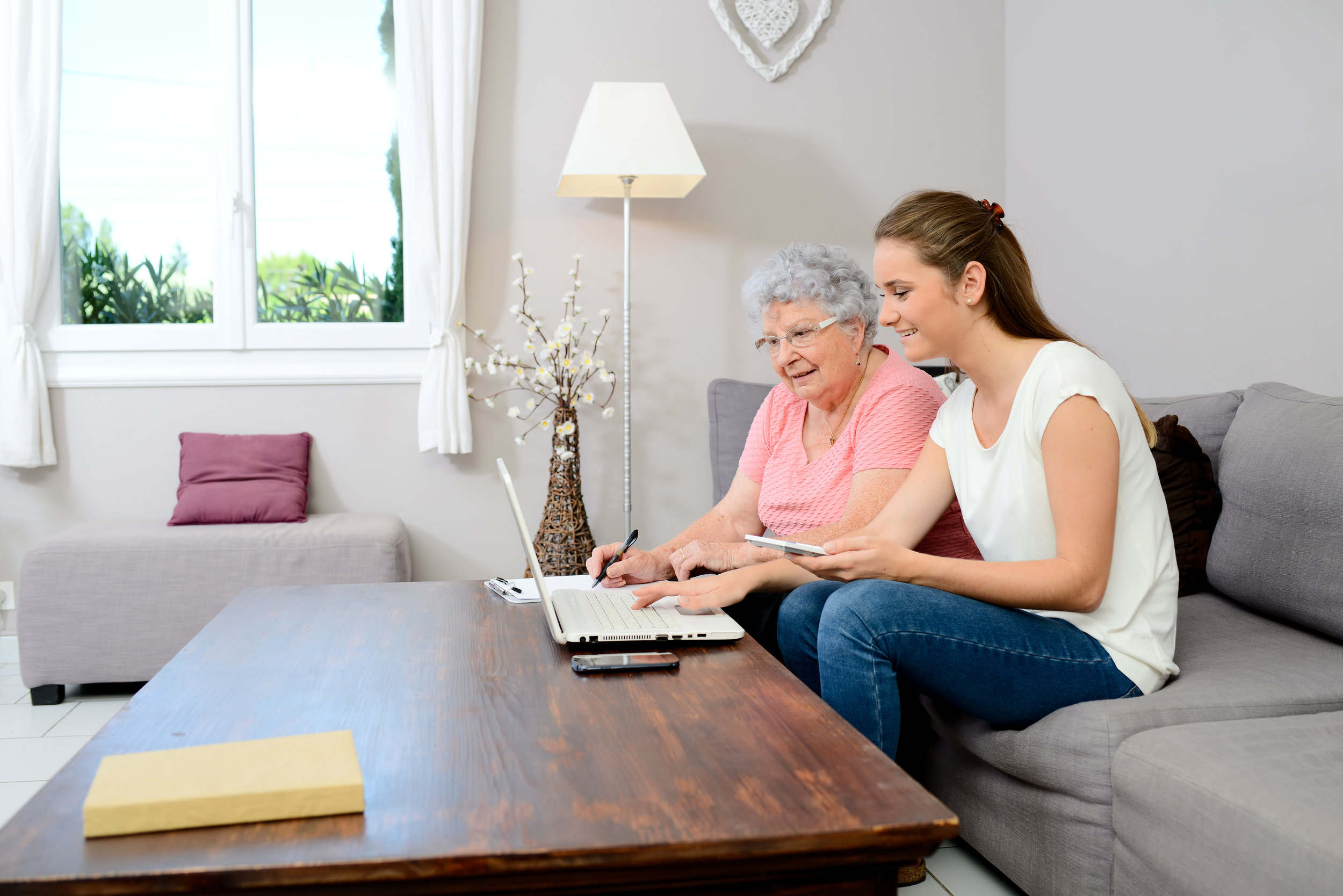 young women helping her elderly mother with her computer