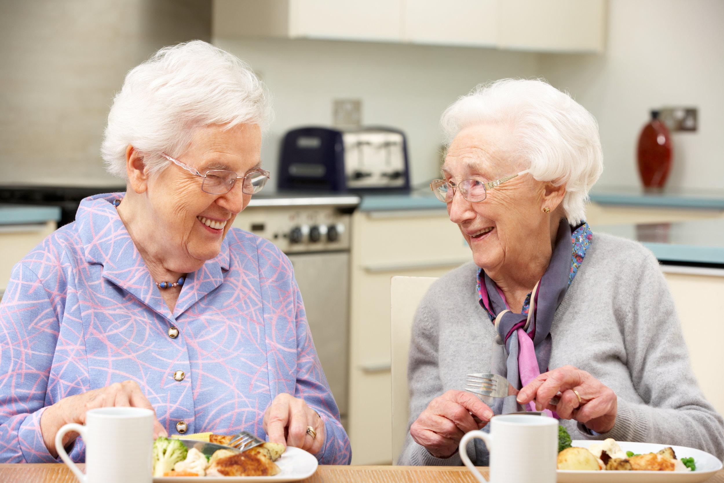 2 elderly ladies having tea and cake