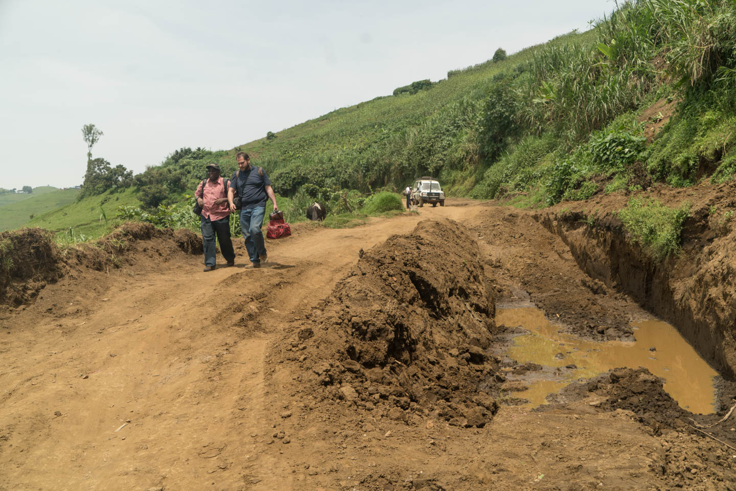 On the road from Misisi, Congo, Fr. Martin Bahati, S.J., and Mr. Luis Vizcano, SJ. walk toward another car that came from Goma to pick them up. The road had been blocked for 3 days because of the mud.
