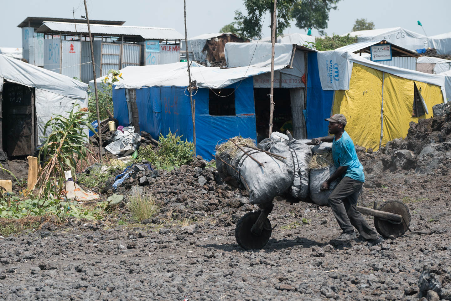 A villager uses a home-made, two wheel cart to move supplies in the refugee camp outside of Goma.