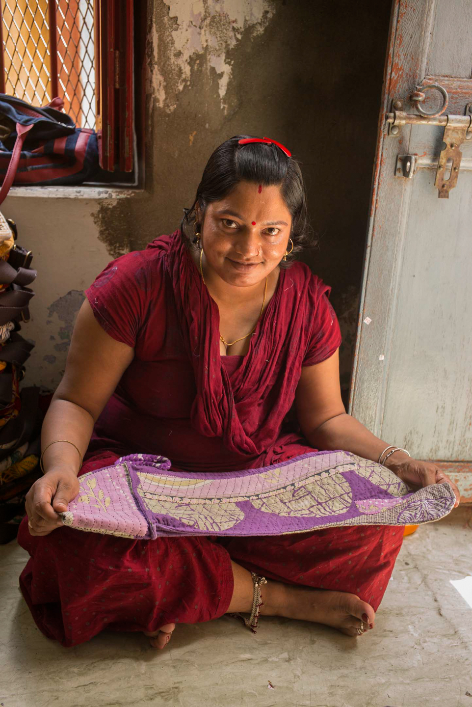 Laxmi, a Sari Bari employee, checks the work and stitching on a finished piece, the final step in the process before sending the work out or to inventory.