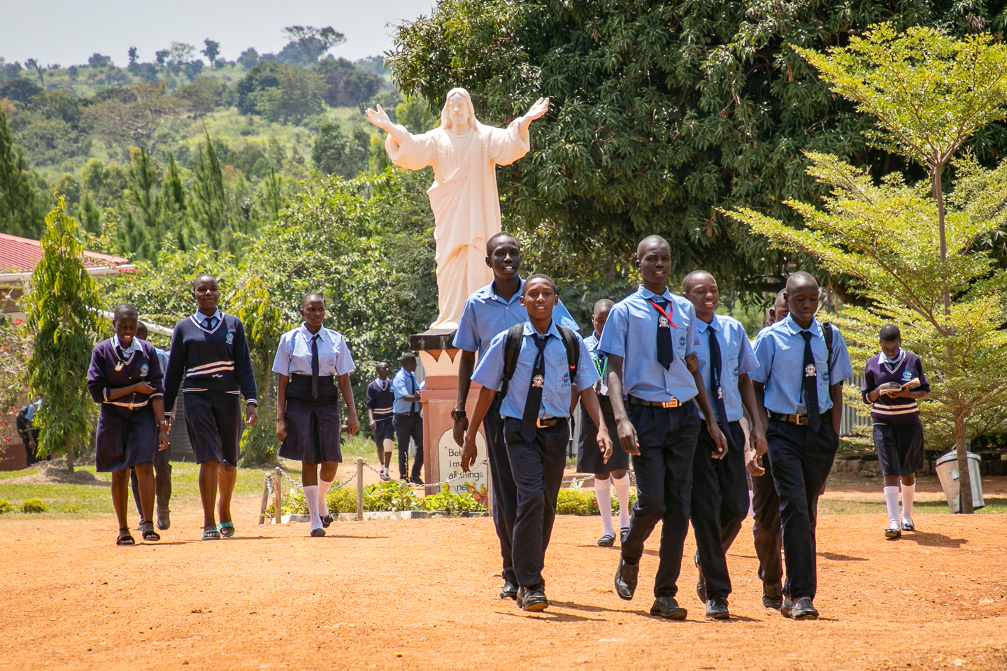 Students Pass Under the Statue of the Risen Christ.
