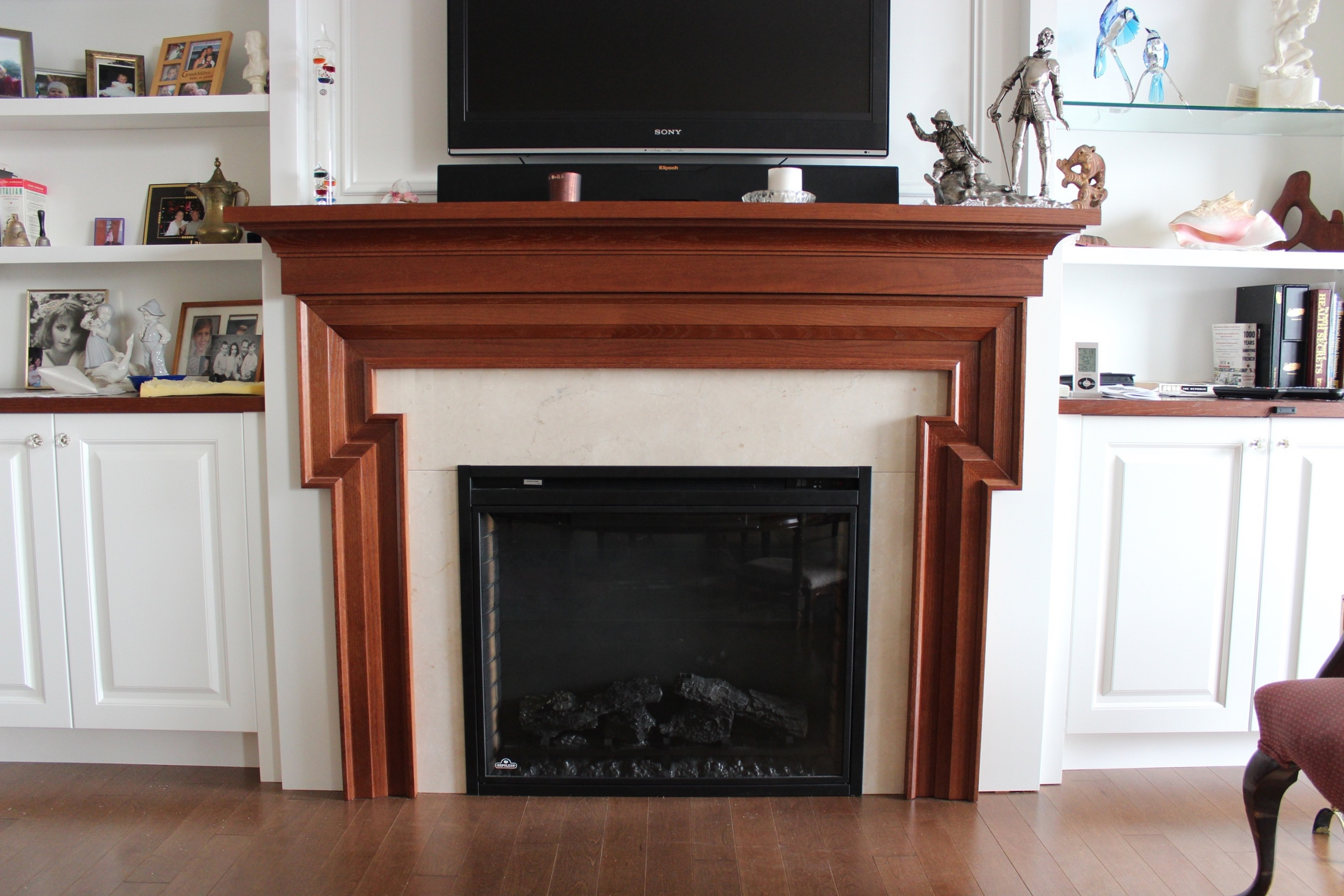 Custom fireplace stained to match furniture. Marble surround with electric fireplace.