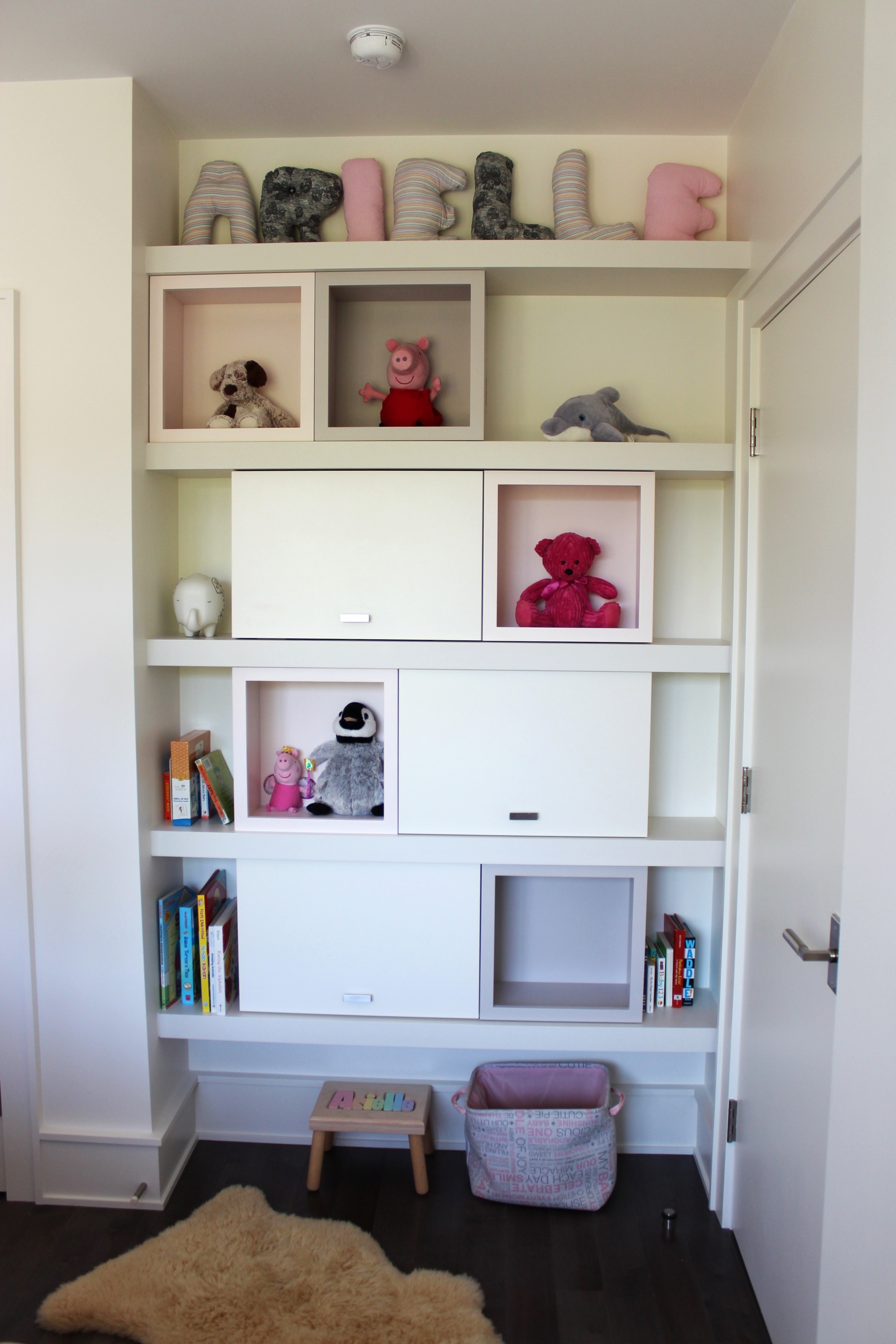 Girl's room used the same concept for storage. Plenty of space for books, toys, and whatever else inside the cabinets!