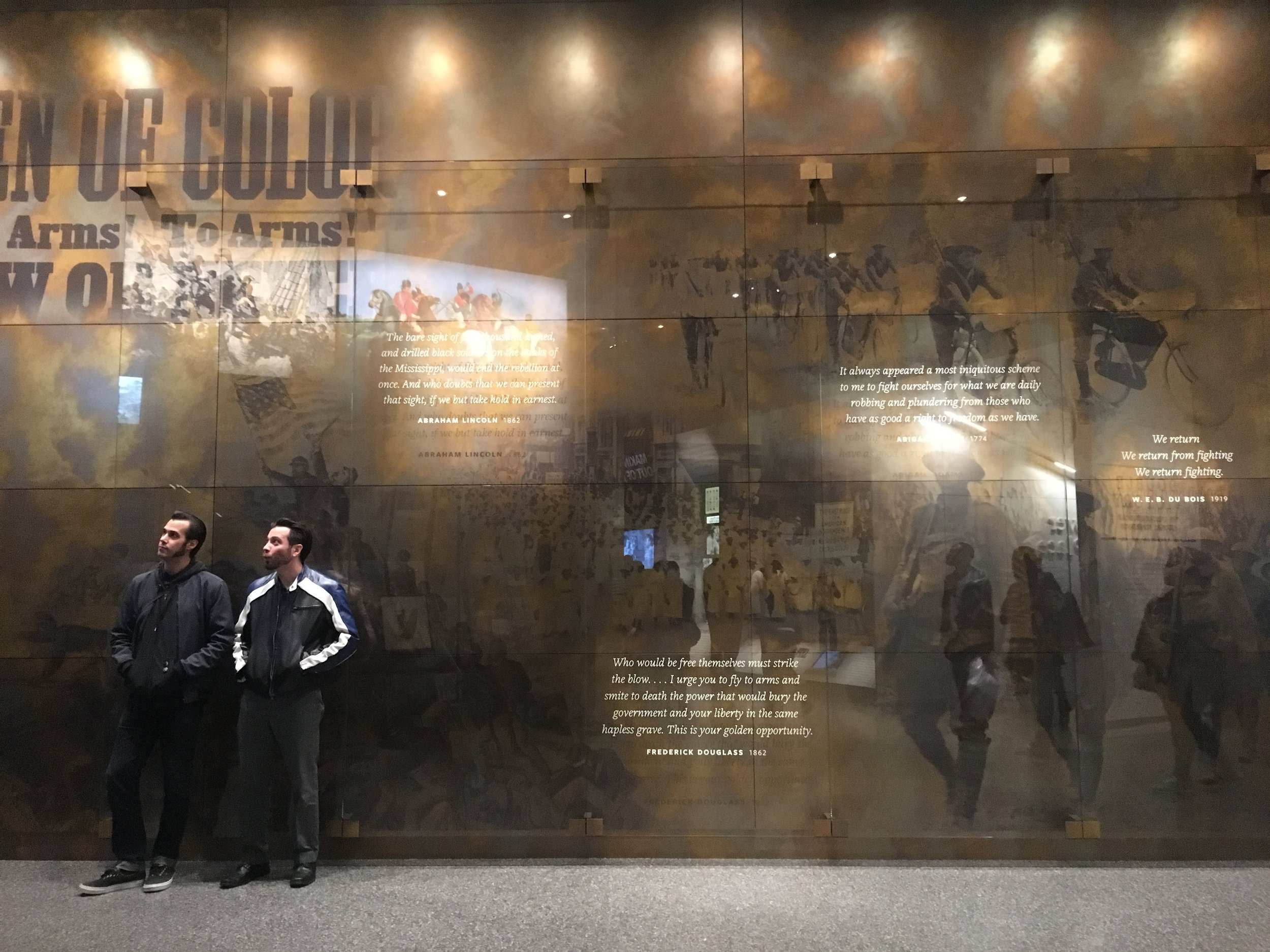 "DOUBLE V. Upon entering the gallery visitors are immediately drawn to the ""Double V"" apex. Visitors will see the 1942 ""Double V"" emblem and an excerpt from the 1948 Executive Order (EO) 9981. Each side of the ""Double V"" apex has five large images and large-print quotations.   Photo credit: Aki Carpenter"