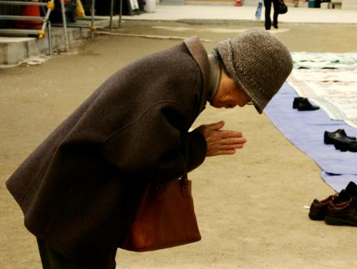 Older woman praying at temple in Seoul