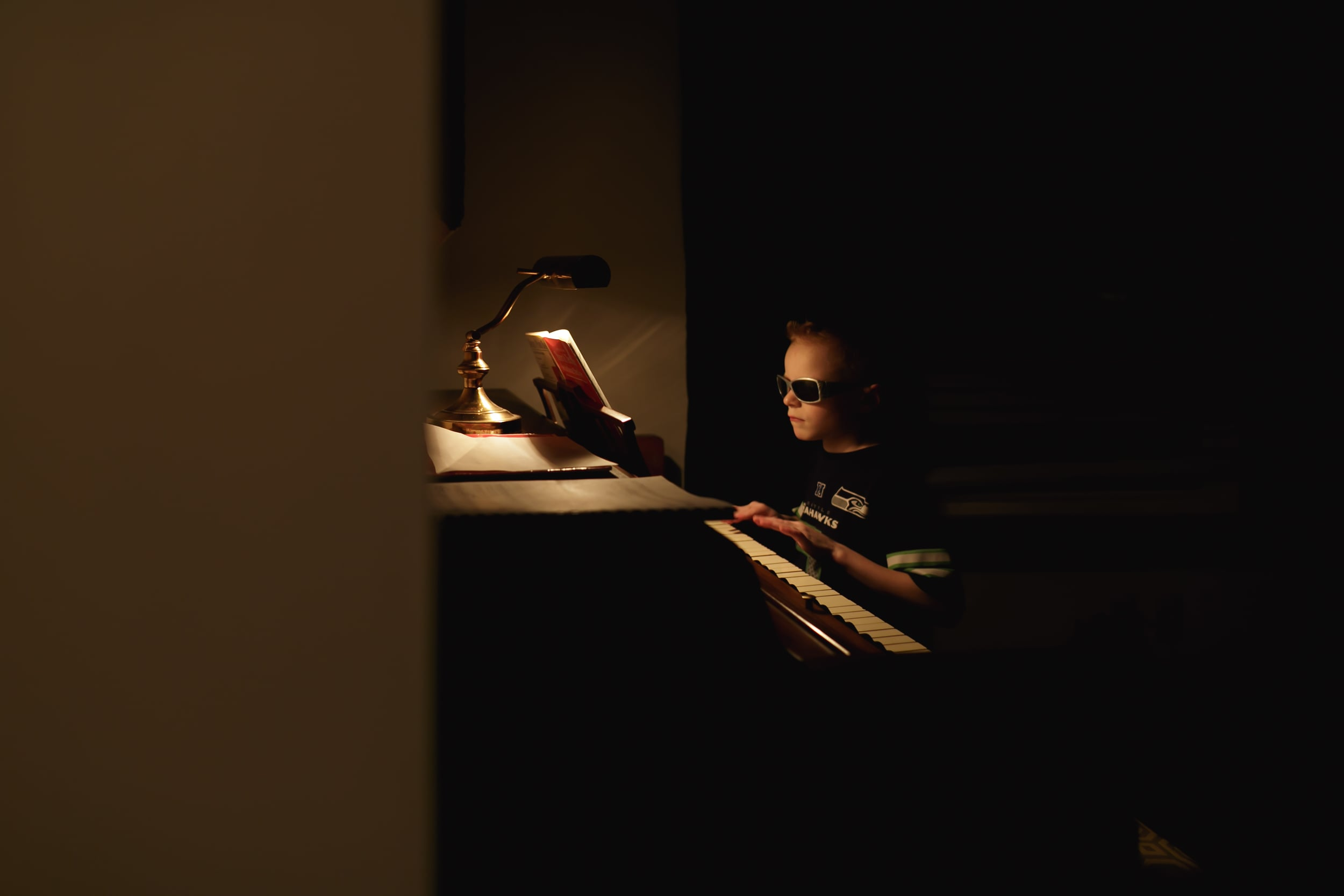 Ben started piano lessons. He's so cool he wears his sunglasses while he practices.