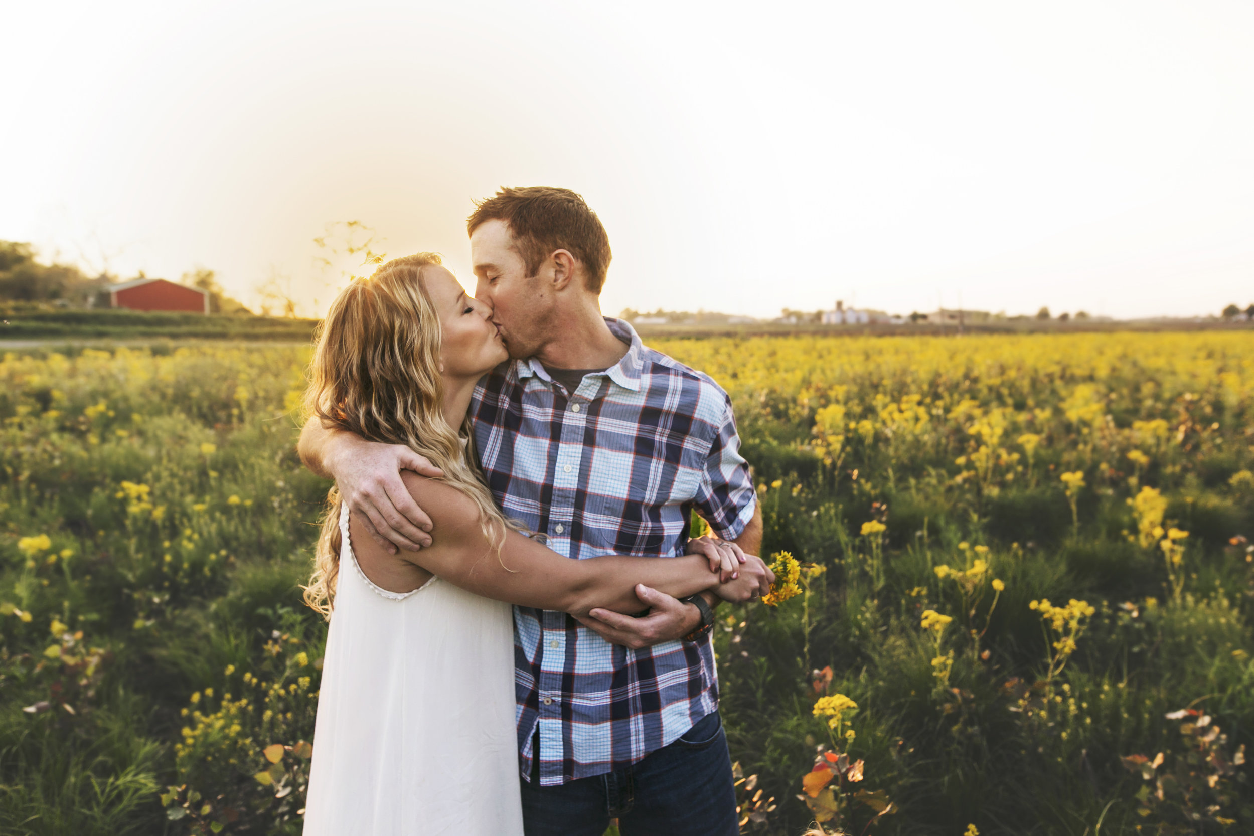 South Bend engagement pictures, family farm, yellow flowers field, red barn, white dress