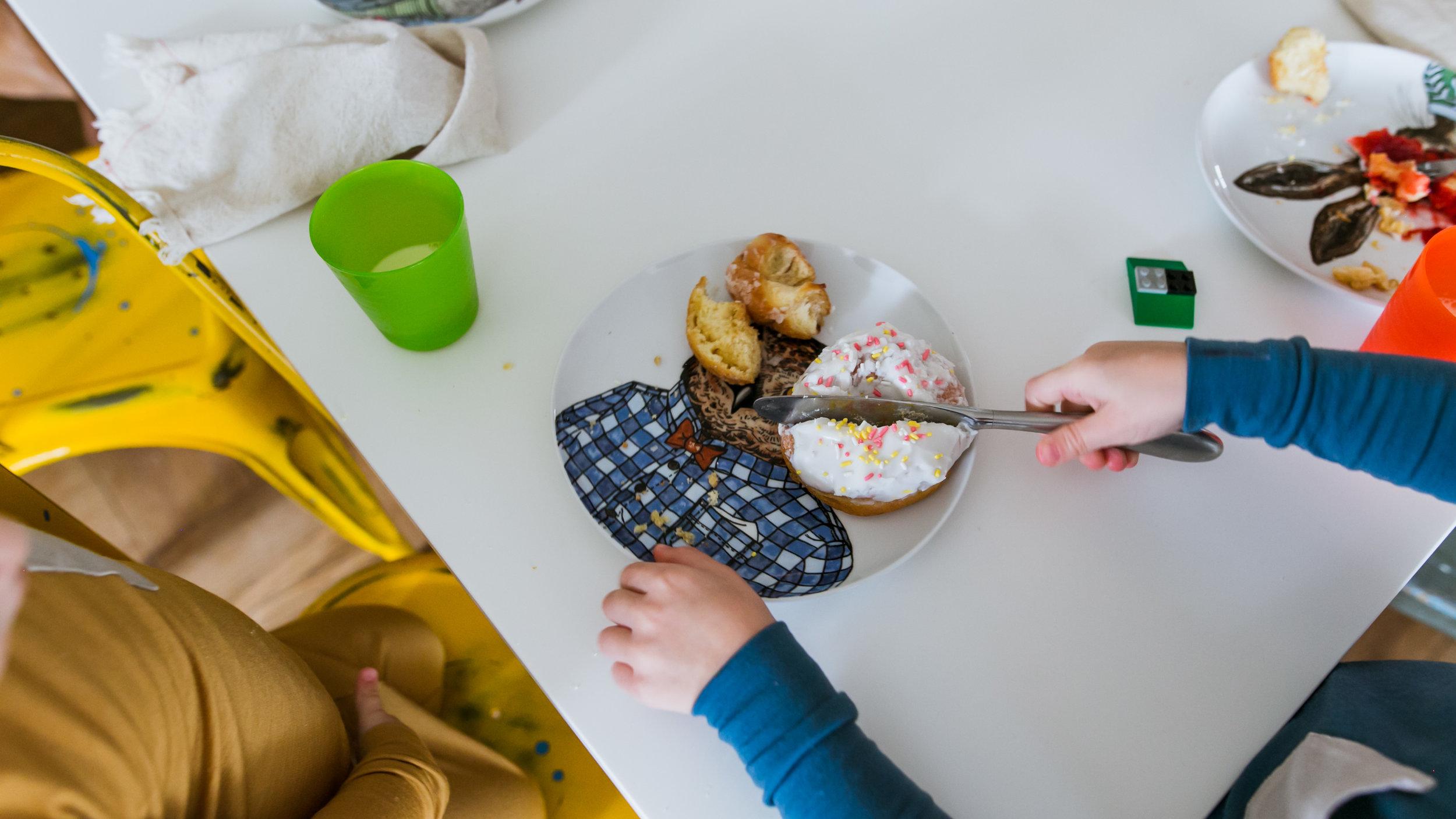 toddler cutting donut in half, family film session mishawaka