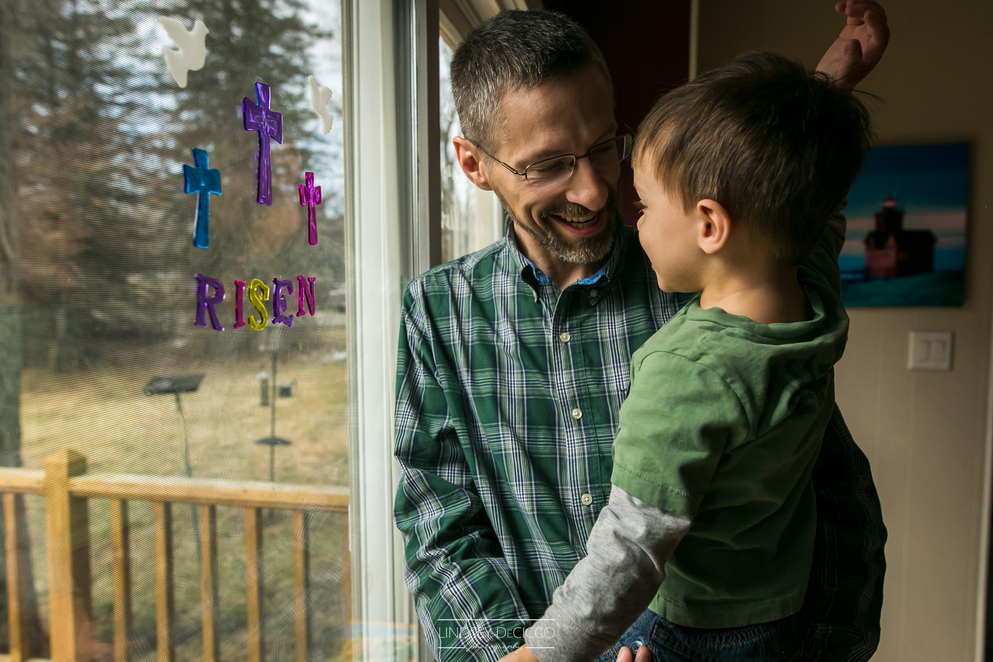 father and son looking at risen sign on window