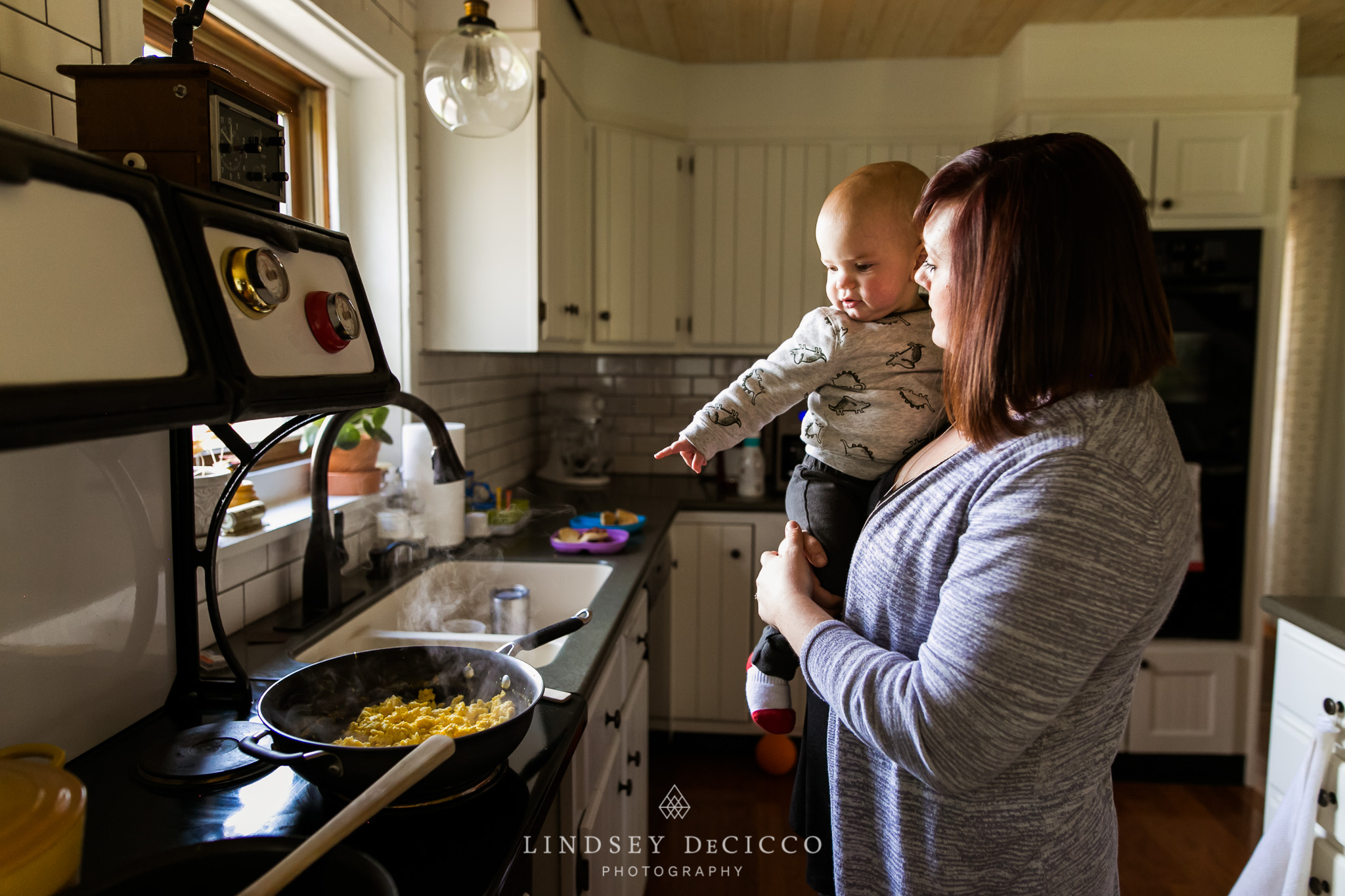 mom cooking with baby on hip