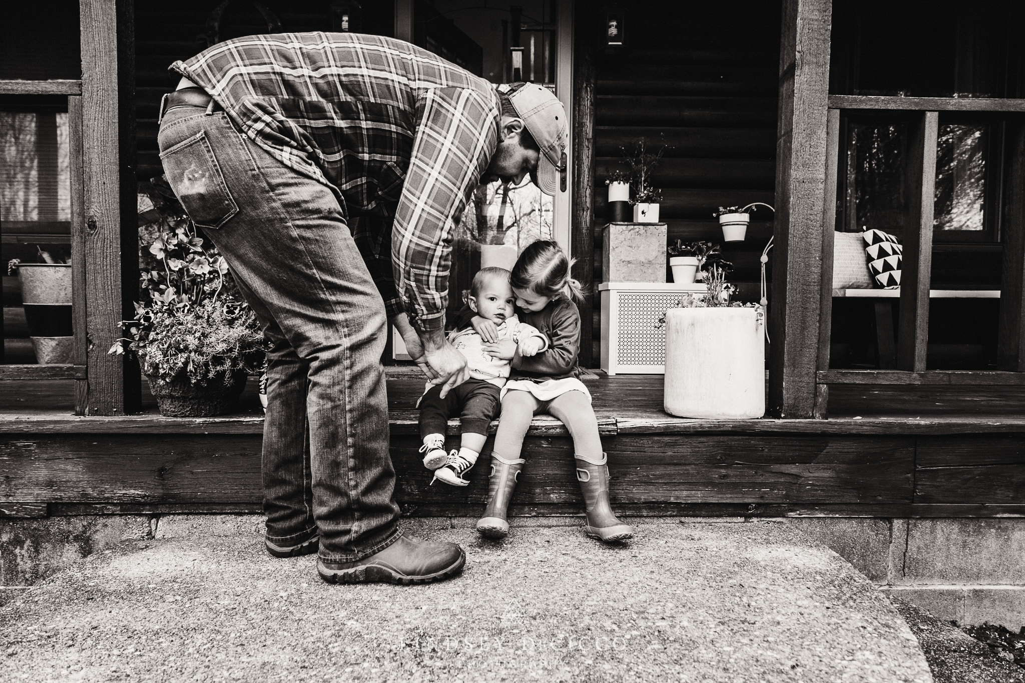 son and daughter with dad on front porch
