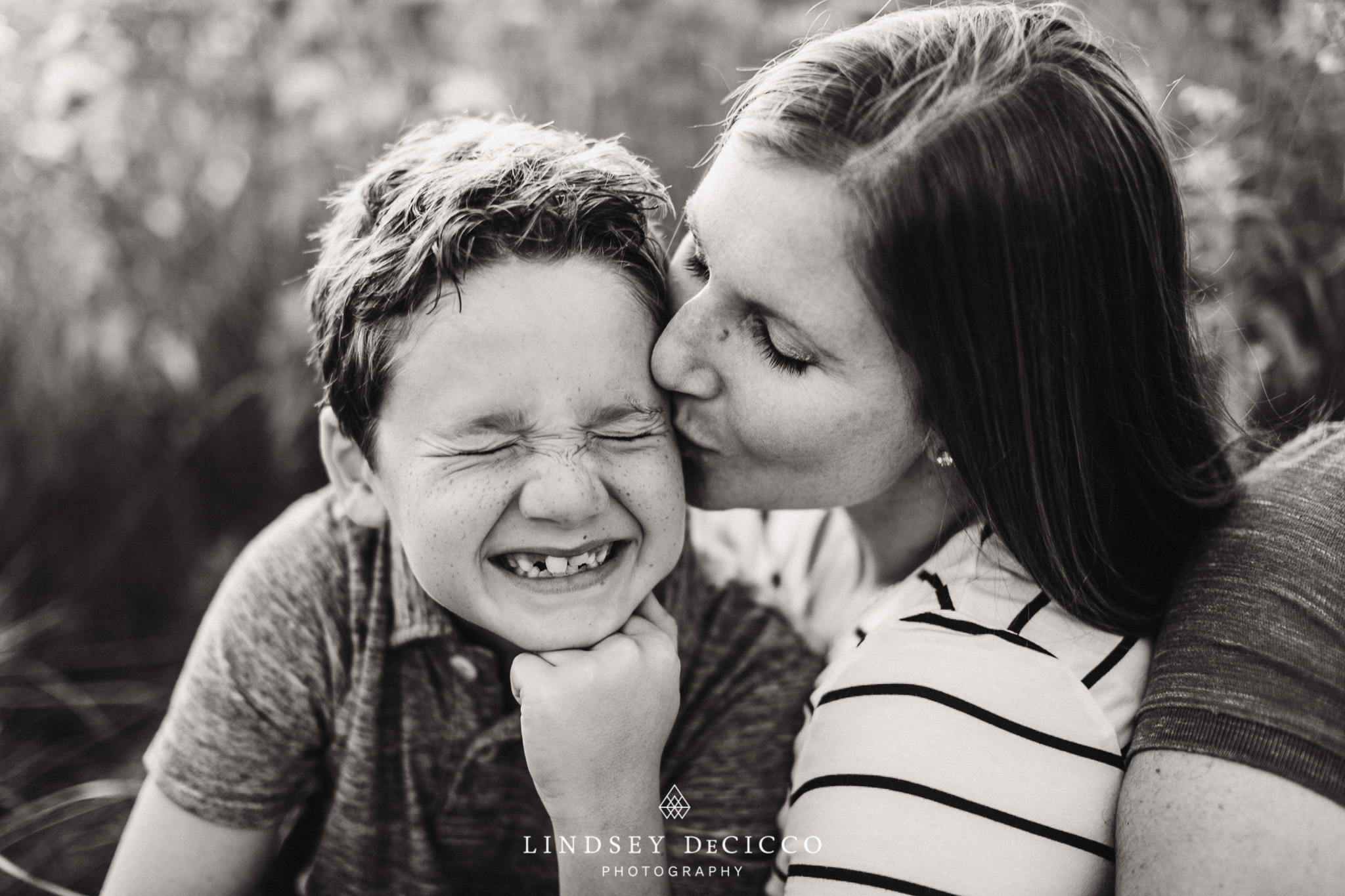 mom and son with freckles not enjoying kiss, black and white