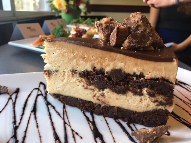 Peanut Butter Brownie Cheesecake - Rich peanut butter and brownie chunk cheesecake layered over a chocolate brownie crust, topped with chocolate ganache and peanut butter cup pieces