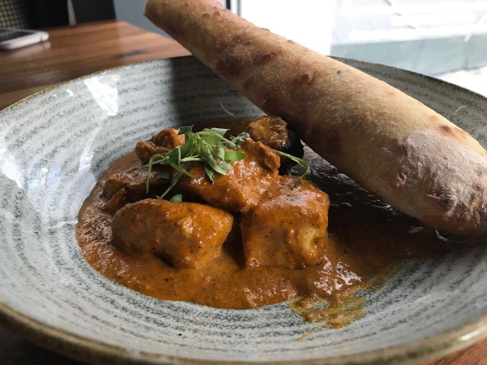 Butter Chicken - Chicken marinated in Indian spices, herb tomato sauce, micro cilantro, garlic naan