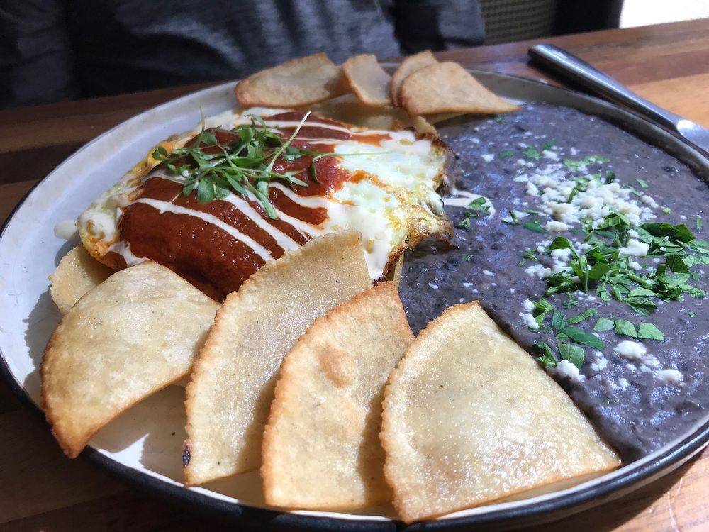Huevos Rancheros - House-made corn and flour tortilla, tomatillo salsa, queso fresco, black beans, topped with a sunny side up egg, sour cream, and cilantro