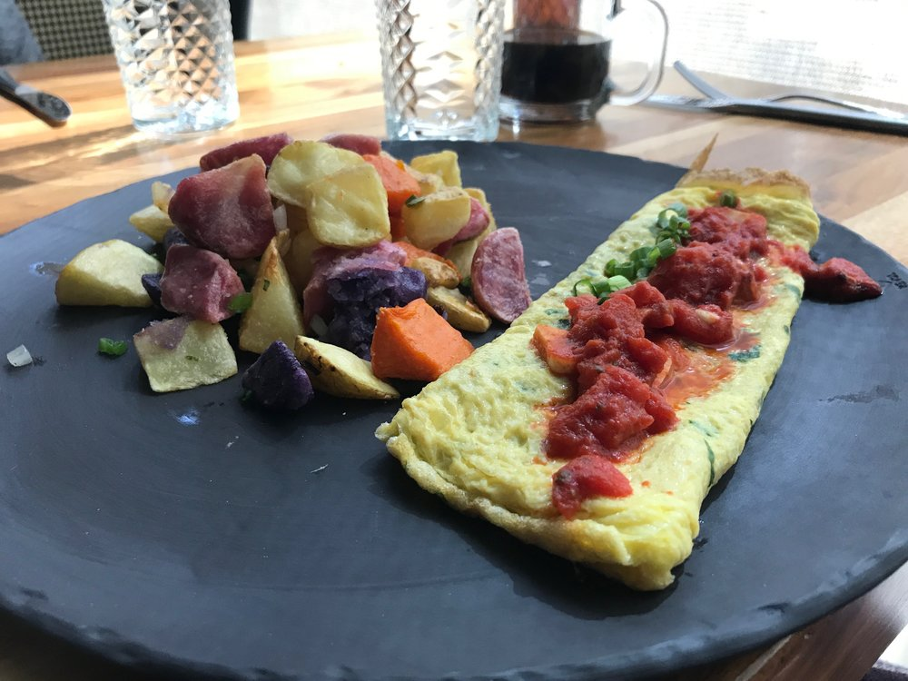 Mediterranean Omelette - Parsley, cilantro, green onion, feta, and tomato confit/served with Essex home fries