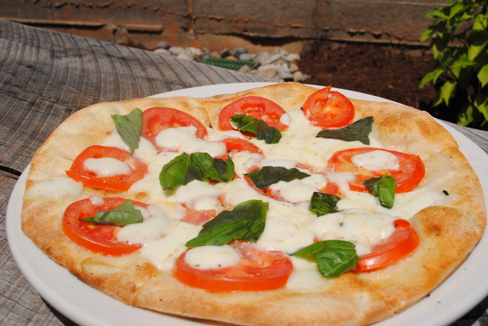 Margherita Pizza - Fresh, house-made mozzarella, Roma tomatoes, and fresh basil on an olive oil base