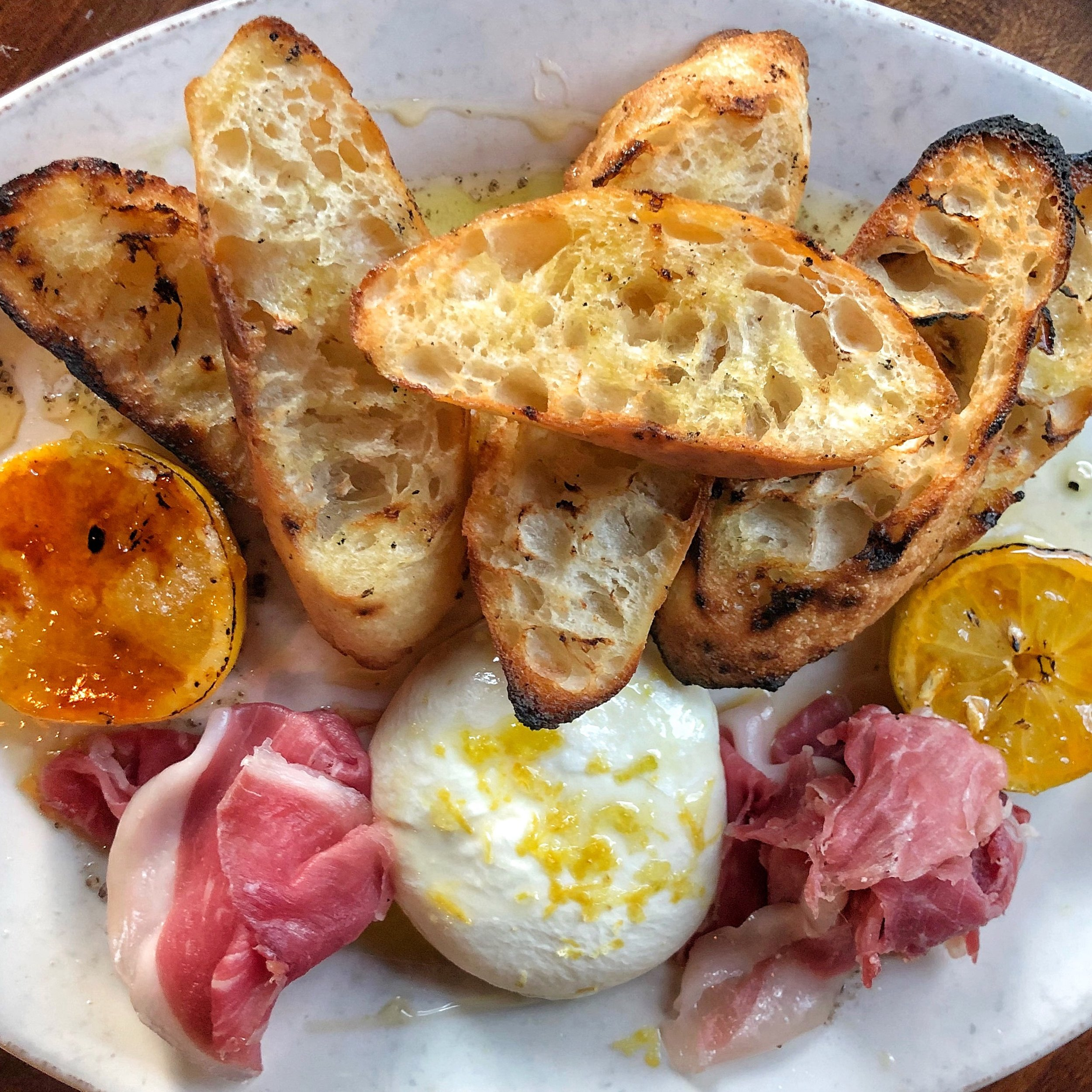 Burrata - housemade burrata with olive oil, smoked salt, brûléed lemon, lemon zest & grilled bread (add proscuitto)