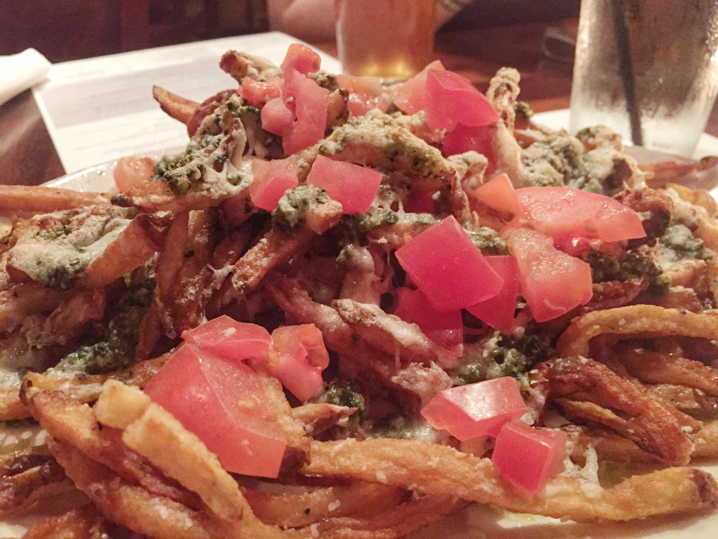 Pesto Brie Fries - hand-cut, twice-fried with pine nut basil pesto, melted brie, tomatoes