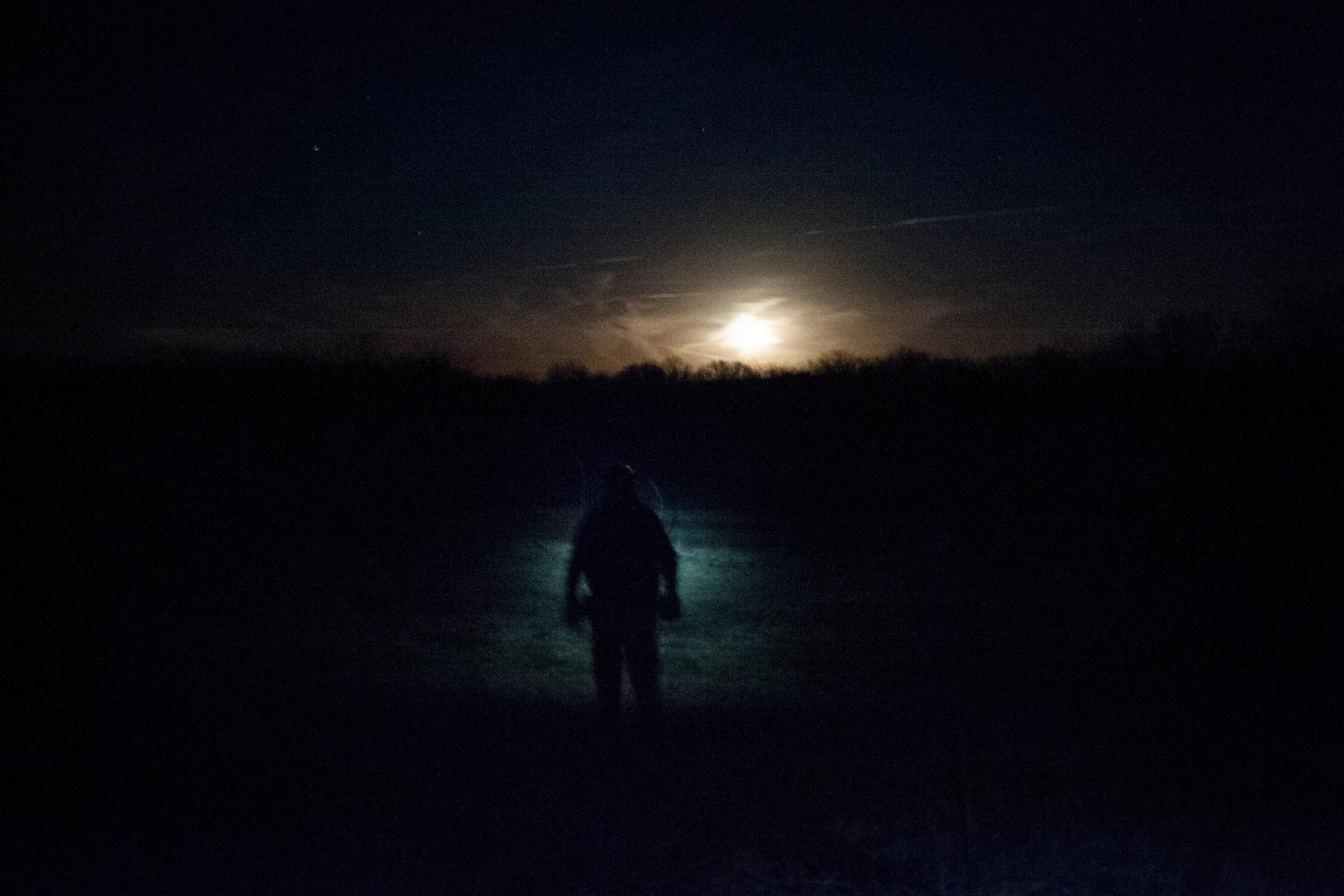 Chris Baker tracks the sound of two of his dogs who have potentially treed a raccoon near Harrisburg, Mo. during a hide hunt in the winter furbearer's season in January, 2014.