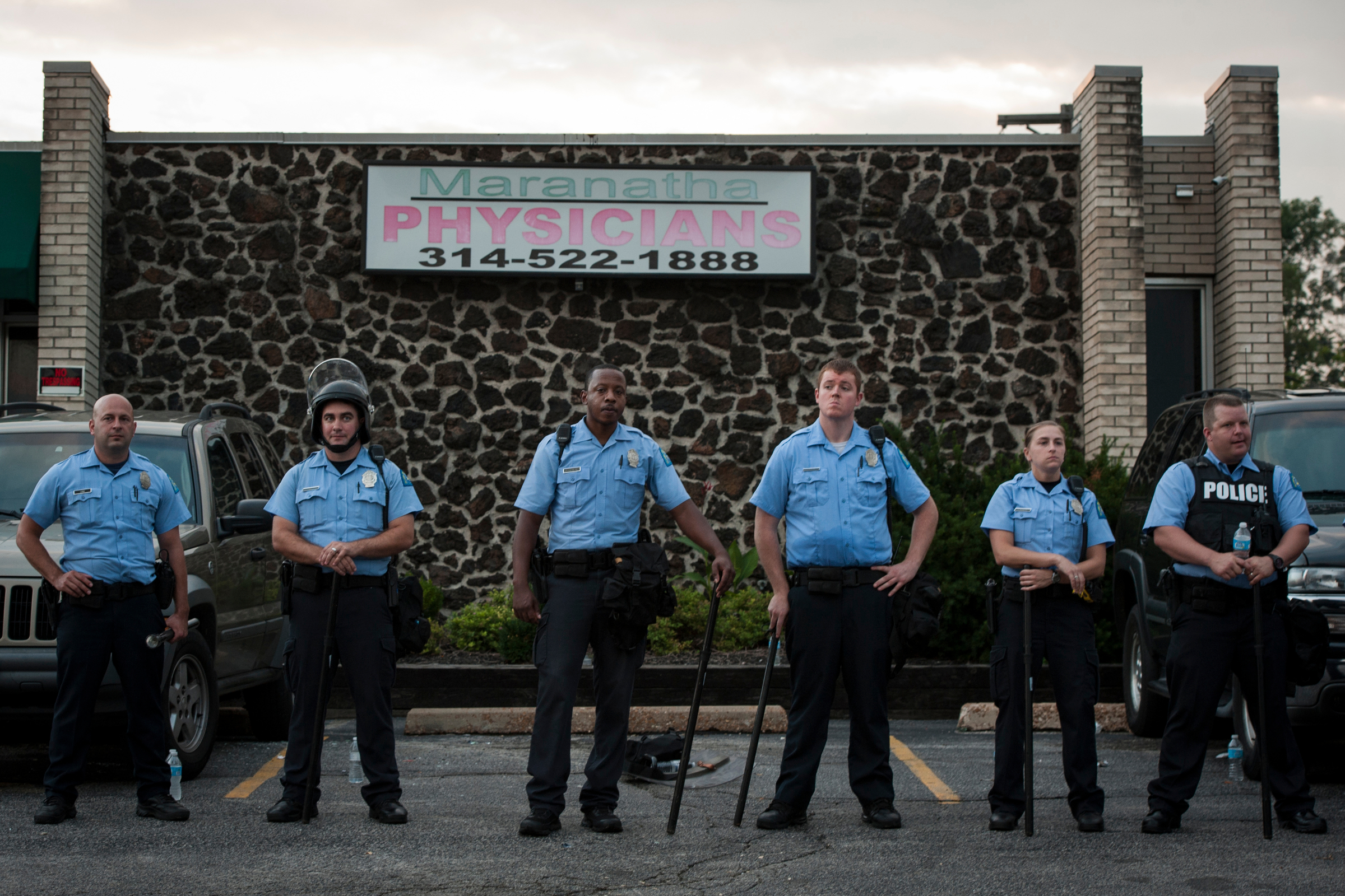 Police officers, some with riot gear, survey the growing crowds and prepare for potentially another night of violent protests in Ferguson, Mo. after a day of peaceful tension in the city. Some business owners armed themselves to prevent repeat looting.