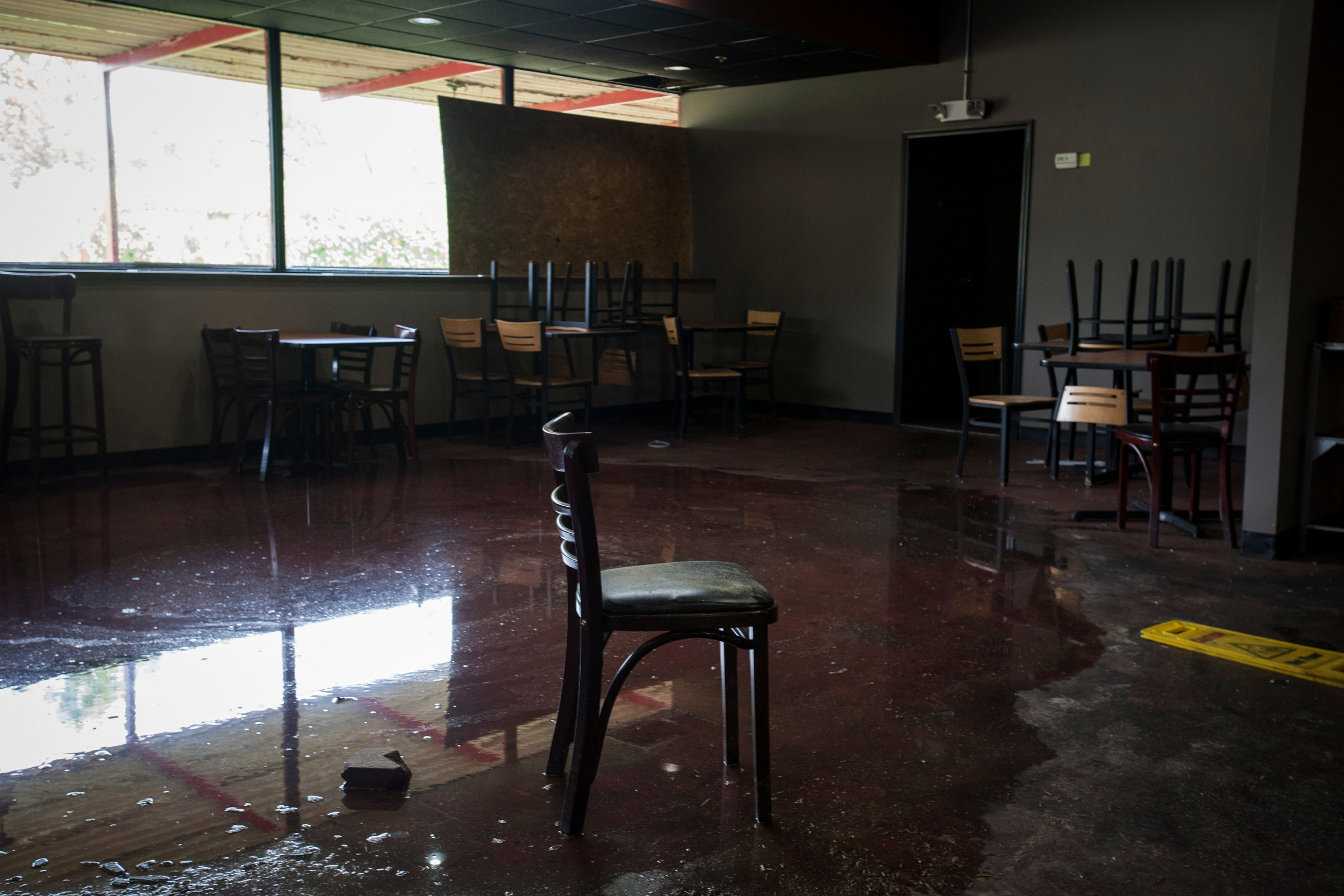 A partially-burned chair sits in a pool of water caused by a sprinkler system that prevented the total distraction of a local restaurant after it was looted and set on fire.