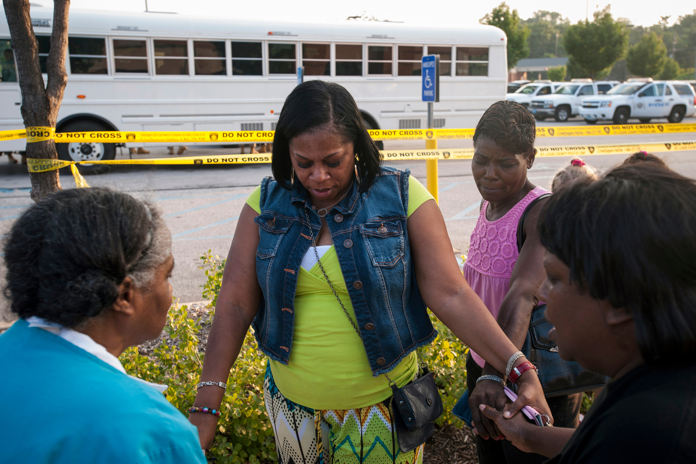 Ferguson residents pray as the National Guard offloads from white busses in response to fears that protestors would march on the police staging location. There was fear that the National Guard themselves would join policing the protests.