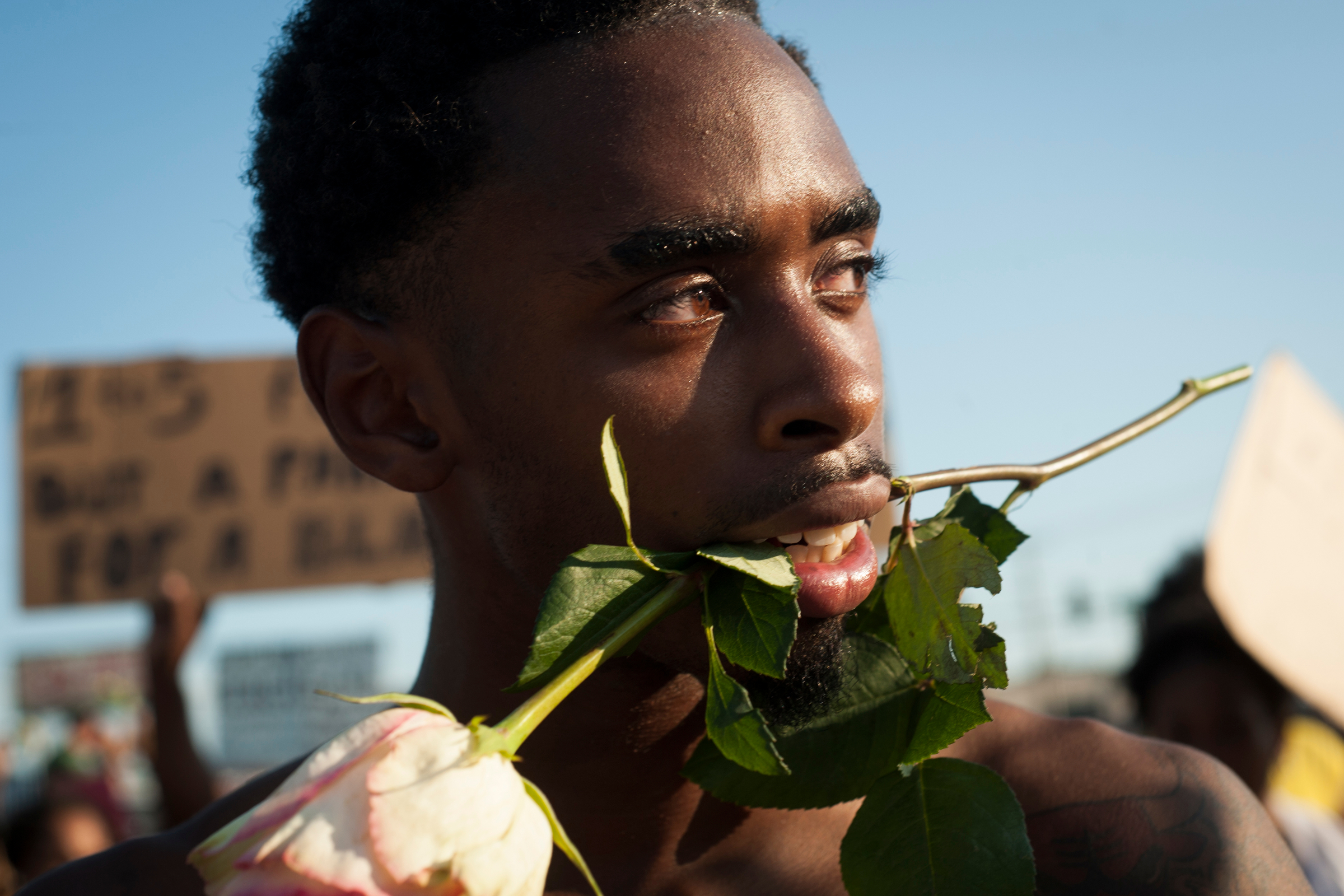 A protestor, who requested to remain unnamed, marches down W. Florissant Ave. in Ferguson, Mo. in one of many early evening protests. Protestors shared roses, some even sharing them with police officers as a peace offering of sorts.