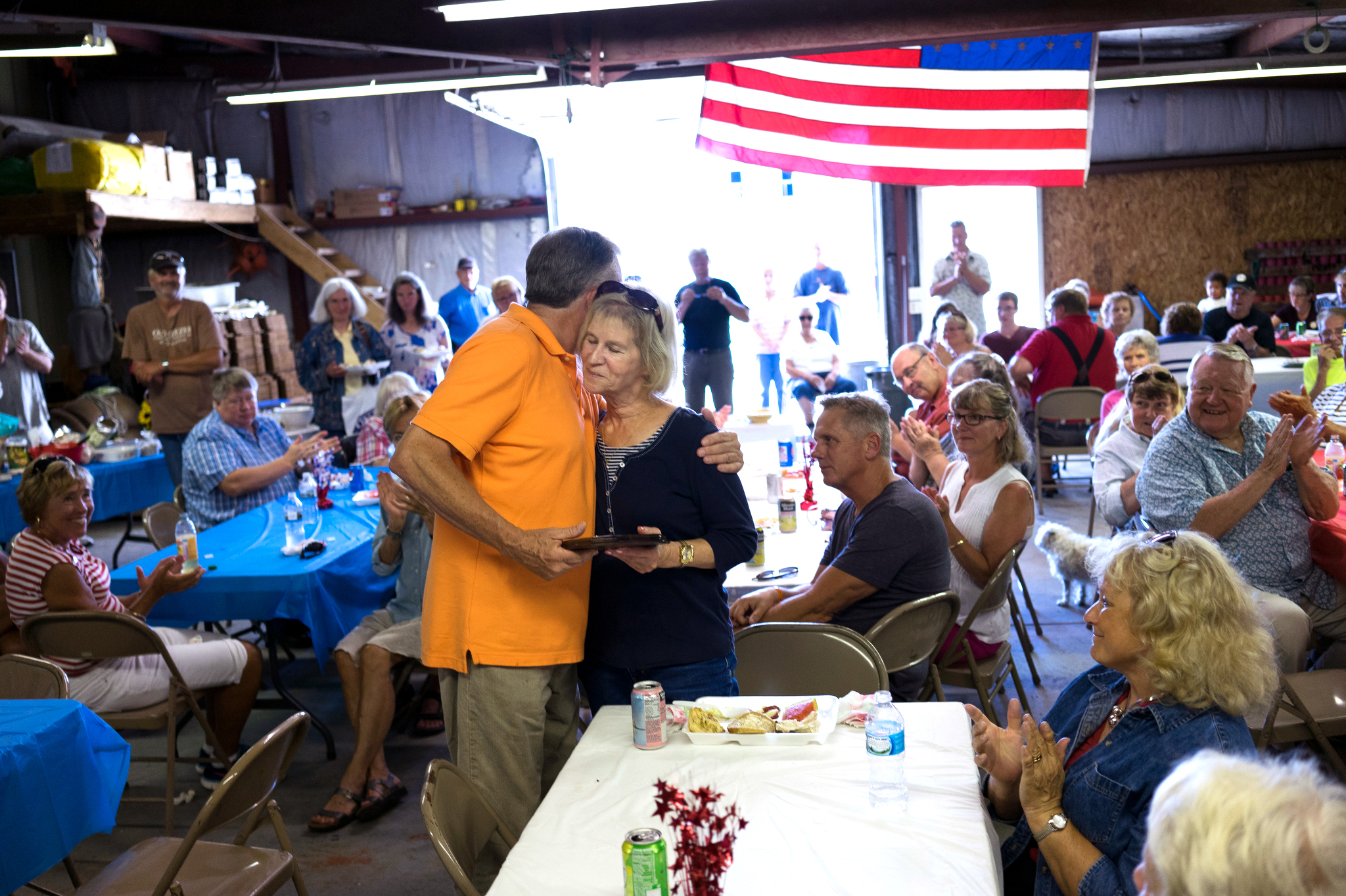 Betty Weborg is presented with a plaque honoring her late husband Jeff, a lifelong fisherman, as the family puts on their annual Labor Day fish boil near the family docks in Gills Rock, WI.