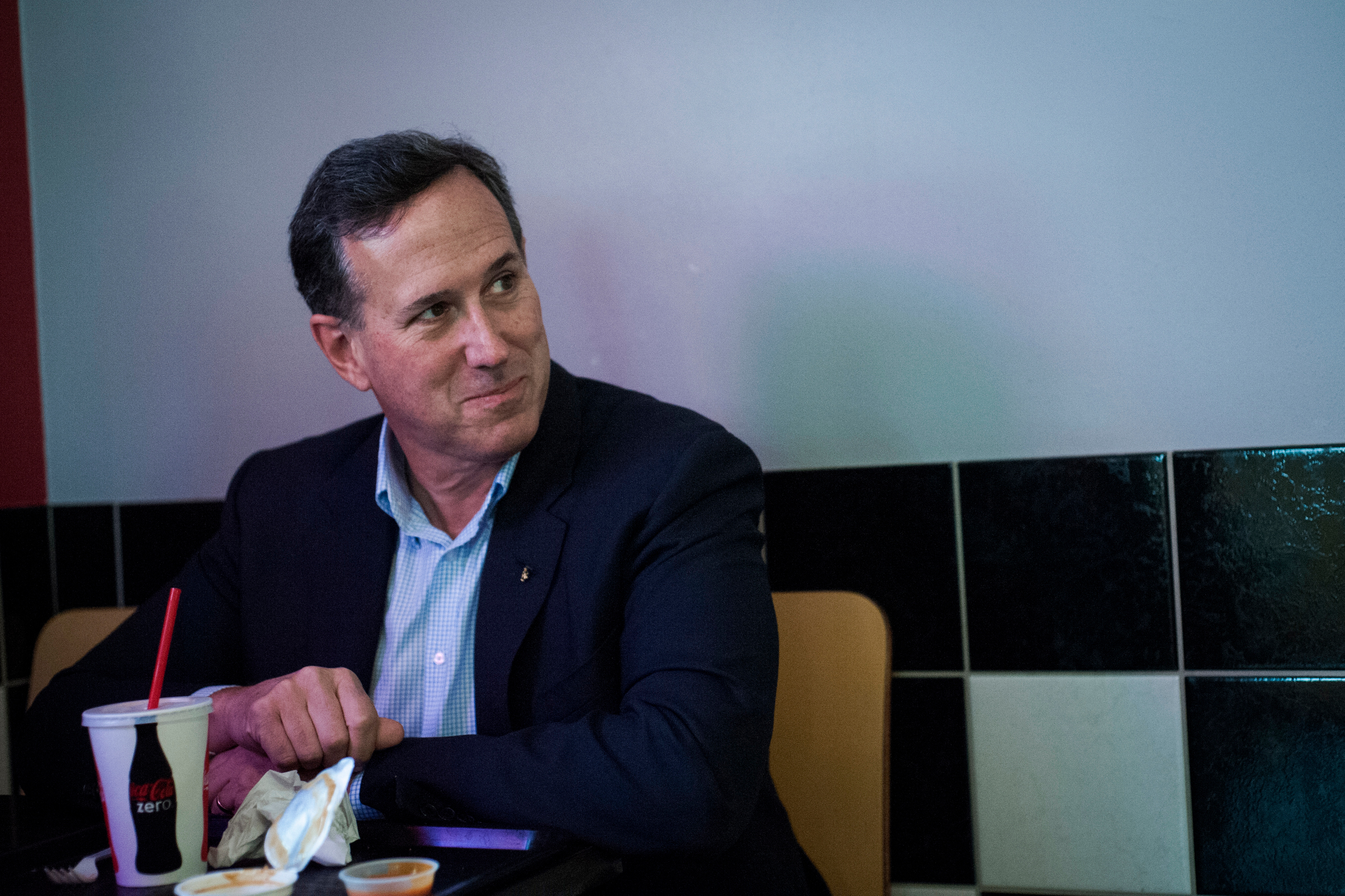 Republican presidential candidate Rick Santorum laughs at joke as he and his staff eat lunch at Bob's Drive Inn between campaign stops.