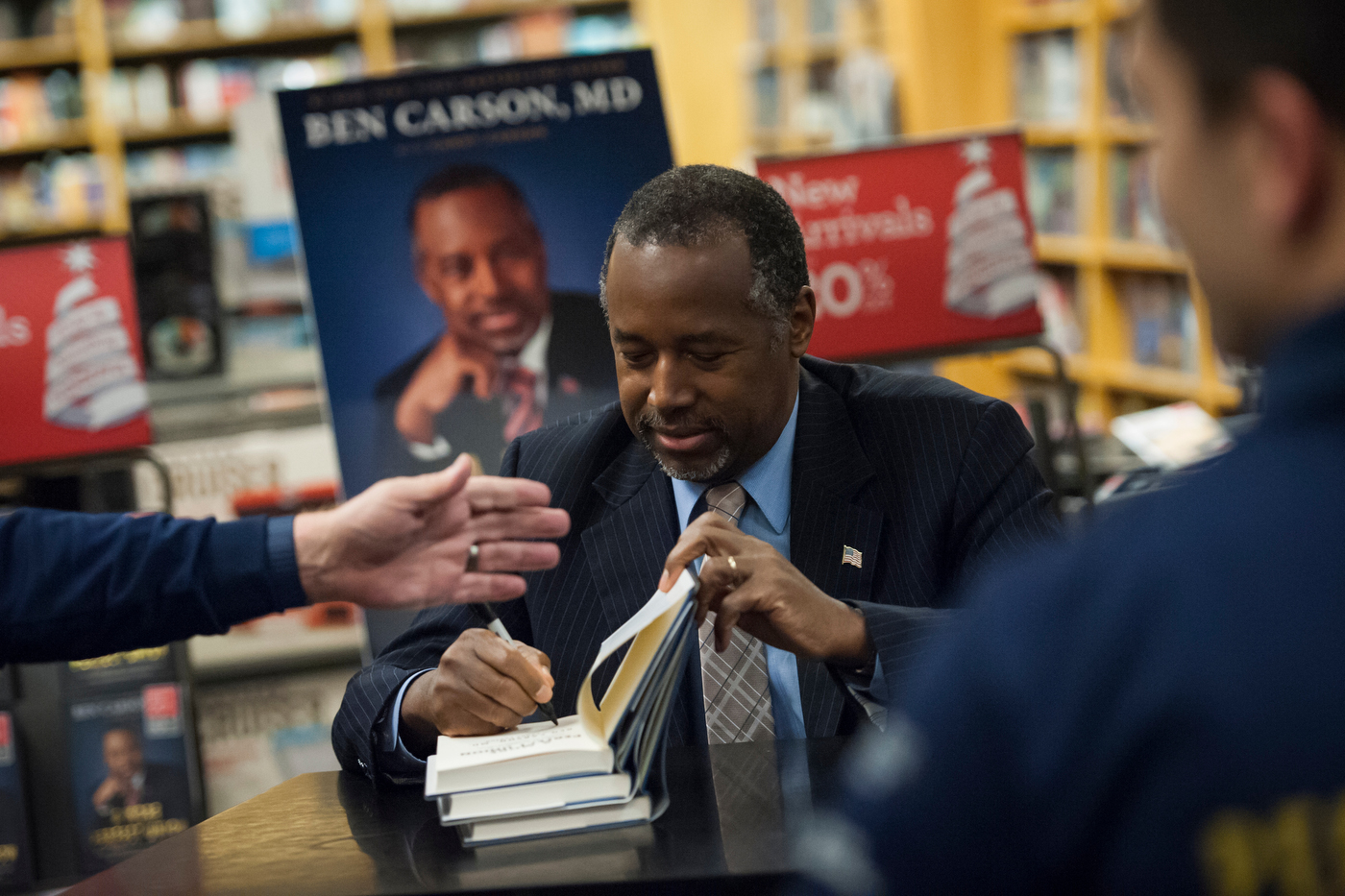 "Republican presidential candidate Dr. Ben Carson signs copies of his book ""A More Perfect Union"" at a book tour stop in Ames, Iowa."