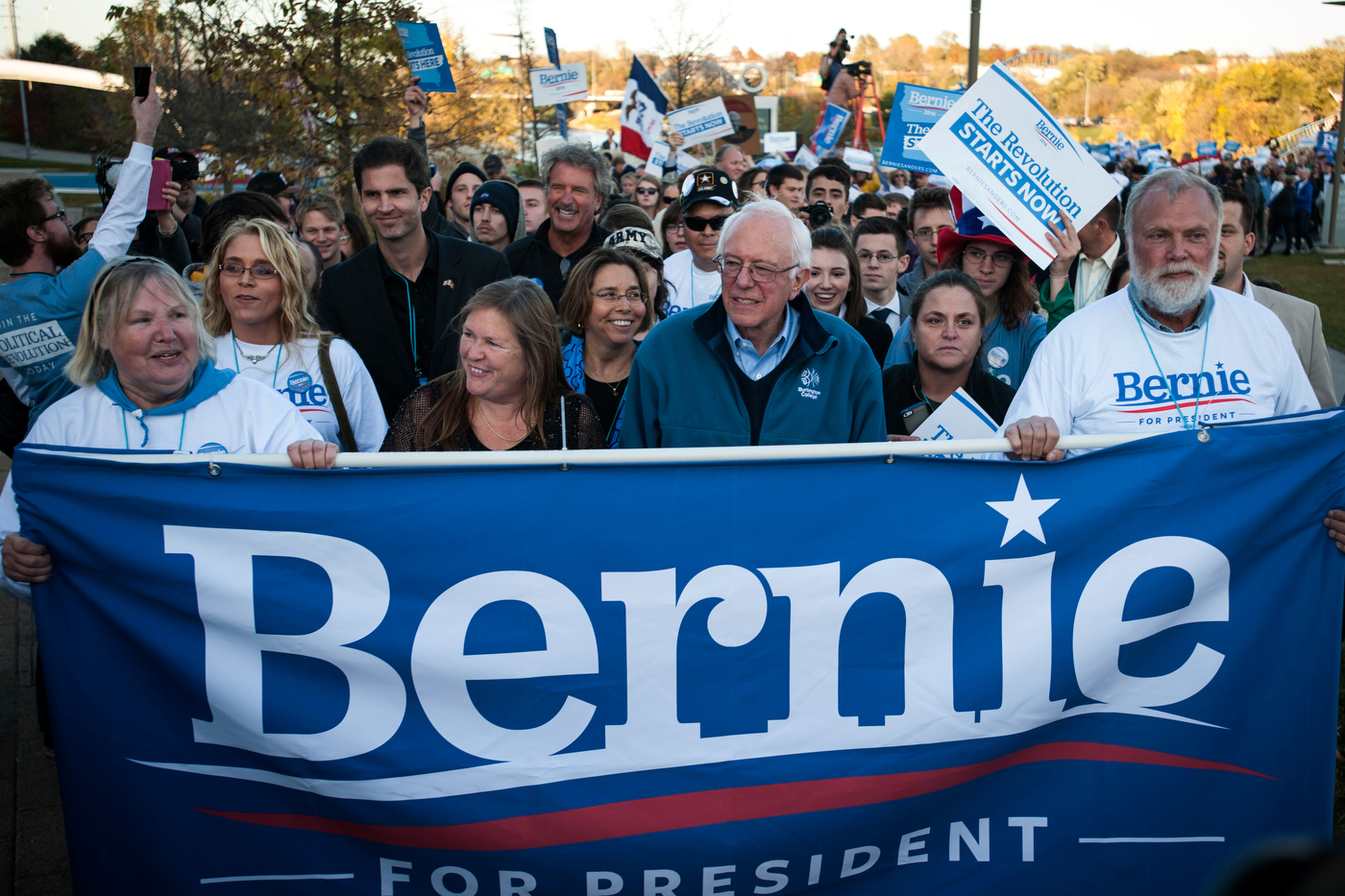 Democratic presidential candidate Sen. Bernie Sanders marches with supporters en route to the Jefferson-Jackson dinner in Des Moines.