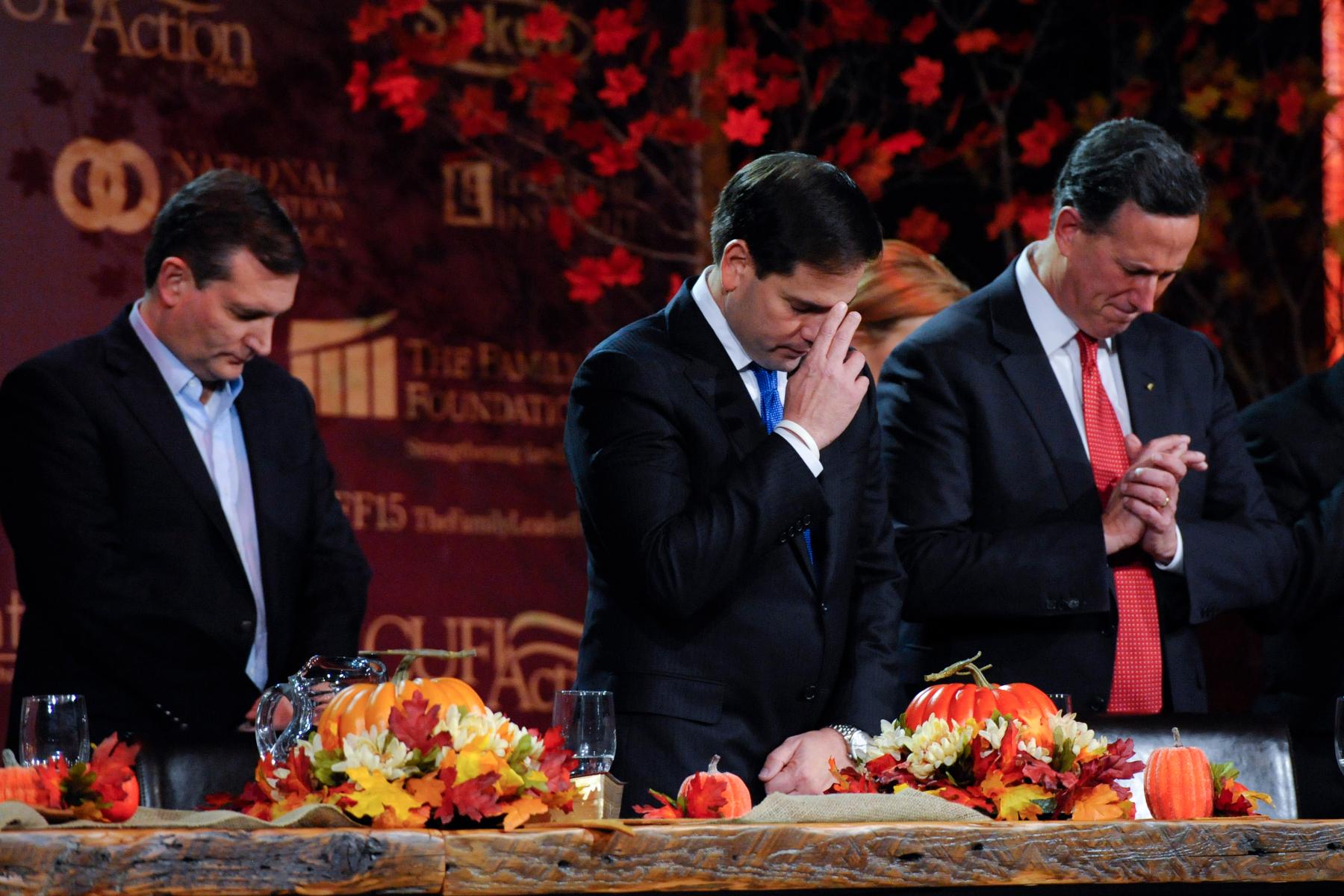Republican U.S. presidential candidates Ted Cruz, Marco Rubio, and Rick Santorum pray at the Presidential Family Forum in Des Moines, Iowa November 20, 2015. REUTERS/Mark Kauzlarich