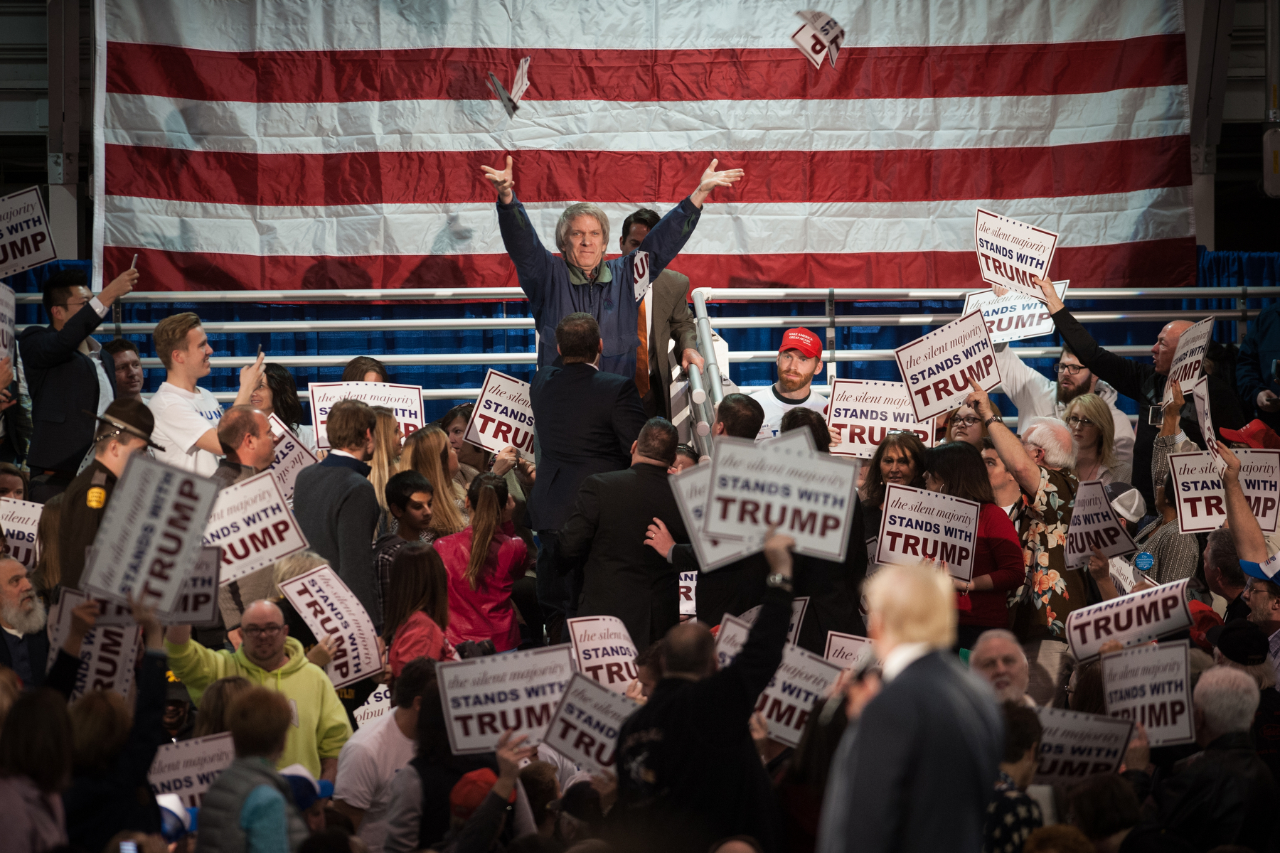 A protestor throws a ripped up campaign sign as Donald Trump, president and chief executive of Trump Organization Inc. and 2016 Republican presidential candidate, speaks during a campaign event in Des Moines, Iowa, U.S., on Friday, Dec. 11, 2015. Mark Kauzlarich/Bloomberg