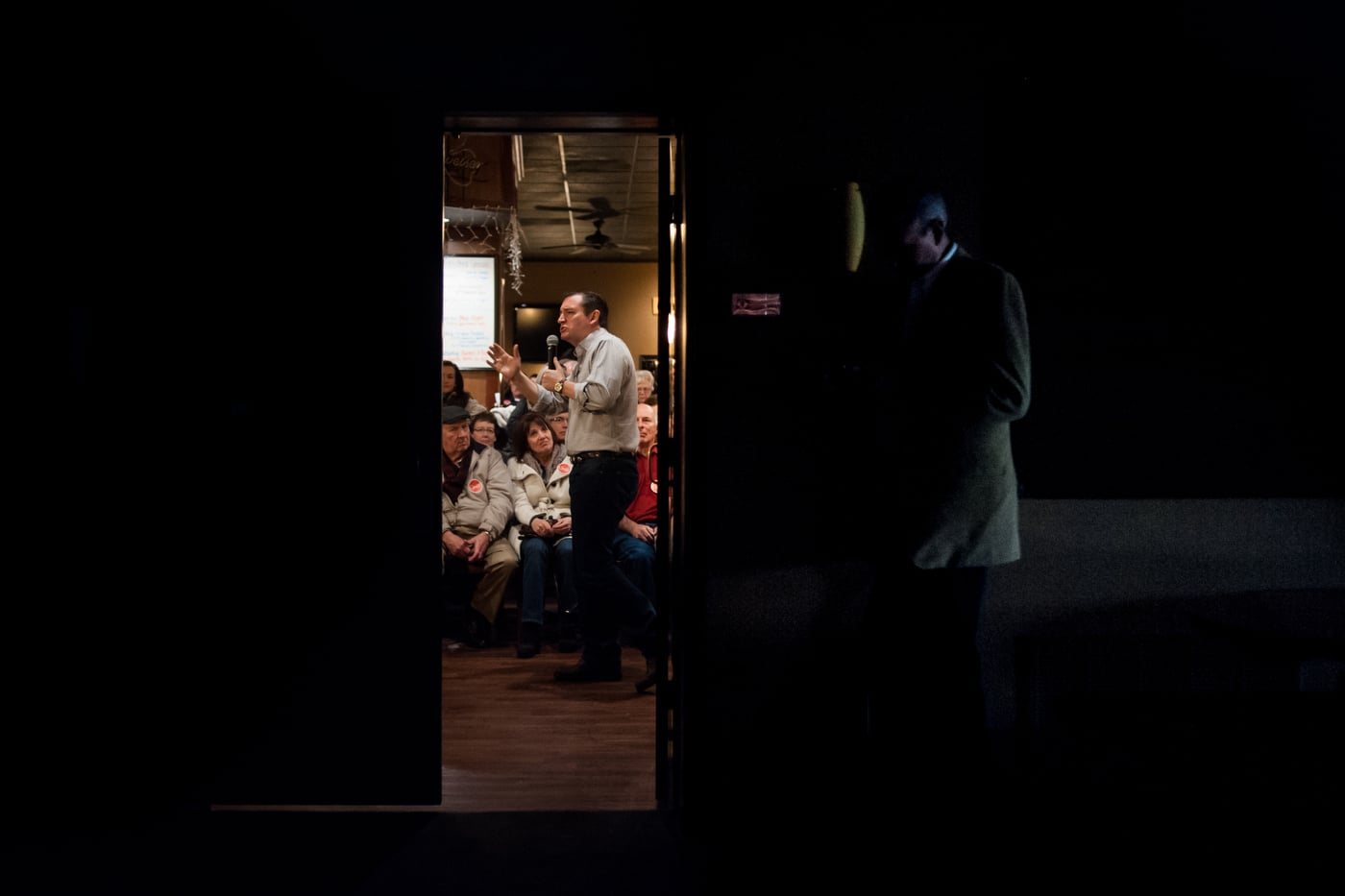 U.S. Republican presidential candidate Ted Cruz is seen from an adjacent room as he speaks at Charlie's Steakhouse at the Carrollton Inn in Carroll, Iowa January 4, 2016. REUTERS/Mark Kauzlarich