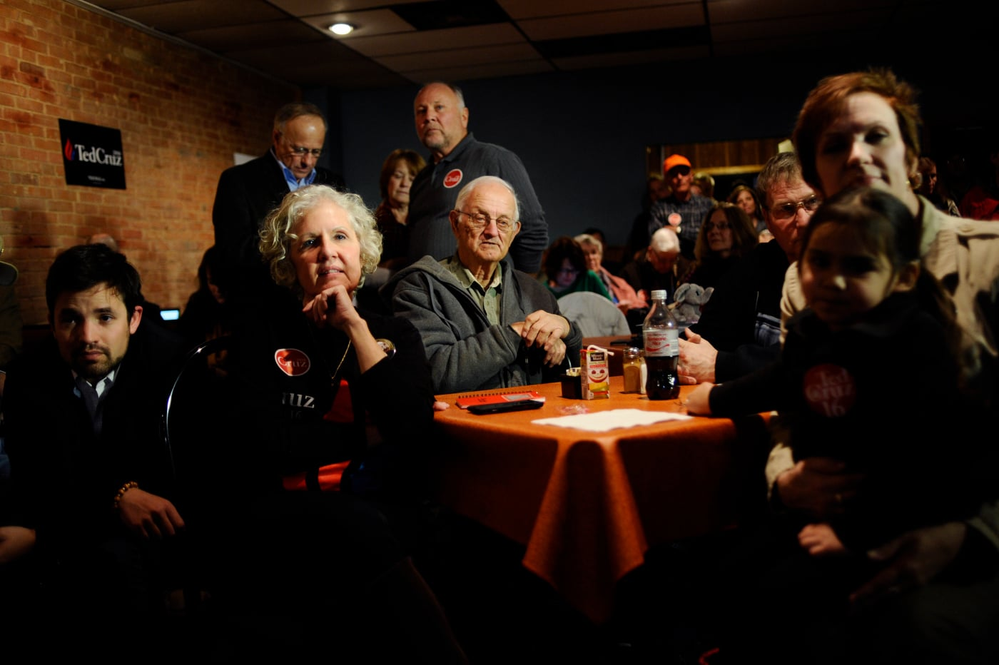 Supporters listen as U.S. Republican presidential candidate Ted Cruz does a live television interview ahead of his campaign stop at Prime Time Restaurant in Guthrie Center, Iowa January 4, 2016. REUTERS/Mark Kauzlarich