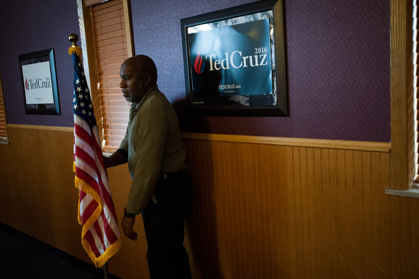 A man adjusts a flag ahead of U.S. Republican presidential candidate Ted Cruz' campaign stop at Godfather's Pizza in Spirit Lake, Iowa January 6, 2016.